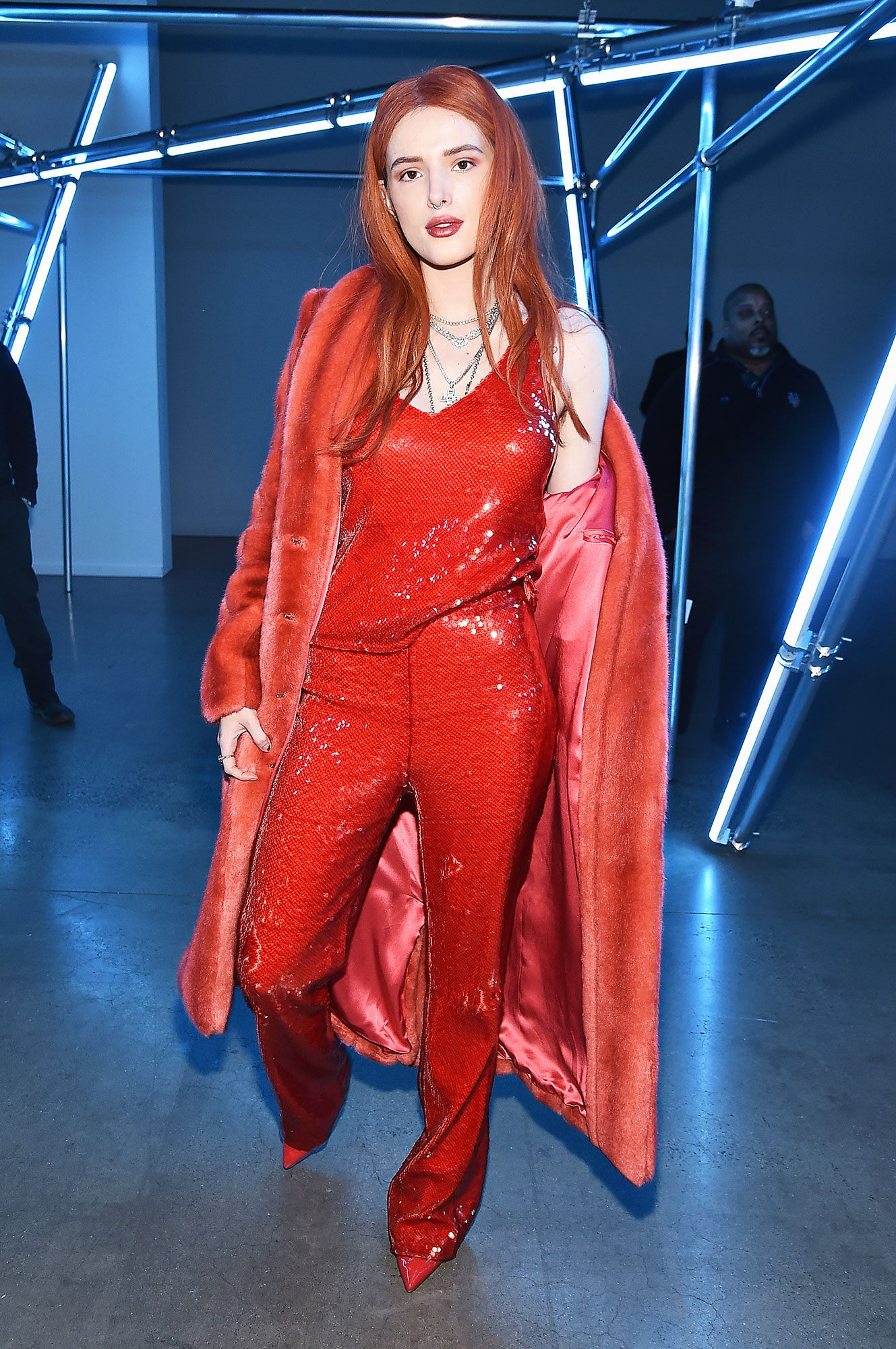 Bella Thorne - Rocking an all-red look, the actress matched her sparkly jumpsuit with pointy heels and a faux fur coat that was as fiery as her hair.