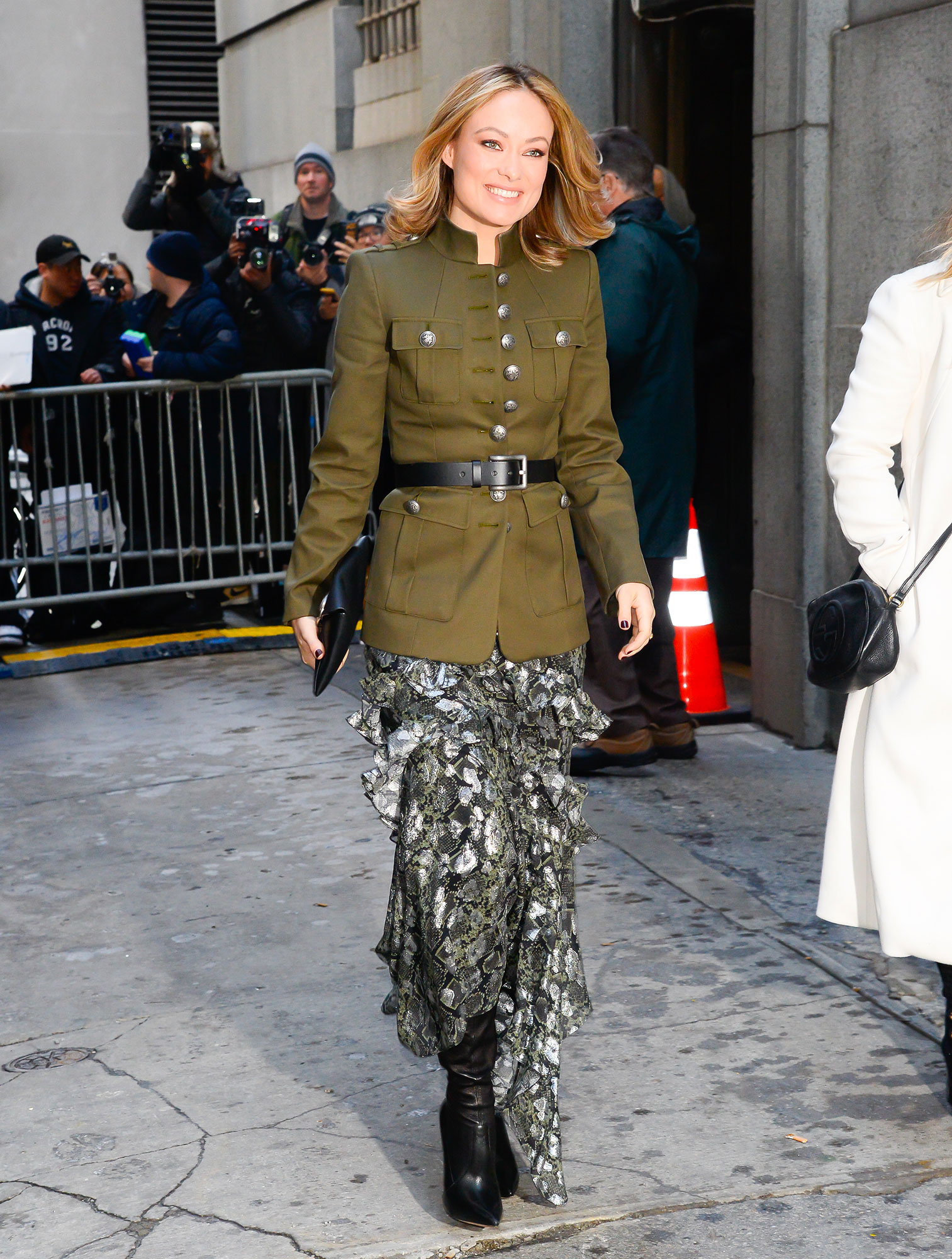 Olivia Wilde nyfw new york fashion week - Giving Us military vibes, the actress wore an ultra-cool olive green jacket over a ruffled silk skirt and black leather boots to the Michael Kors show on February 13.