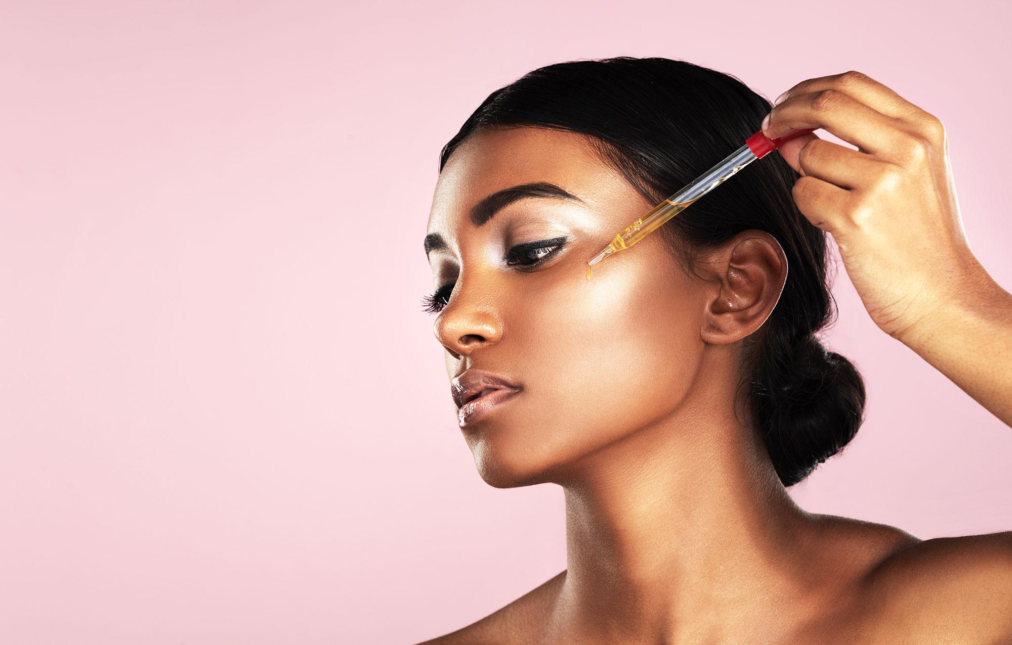 Woman applying serum to her face Splurge vs. Save: Lux Skin Care - Woman applying serum to her face