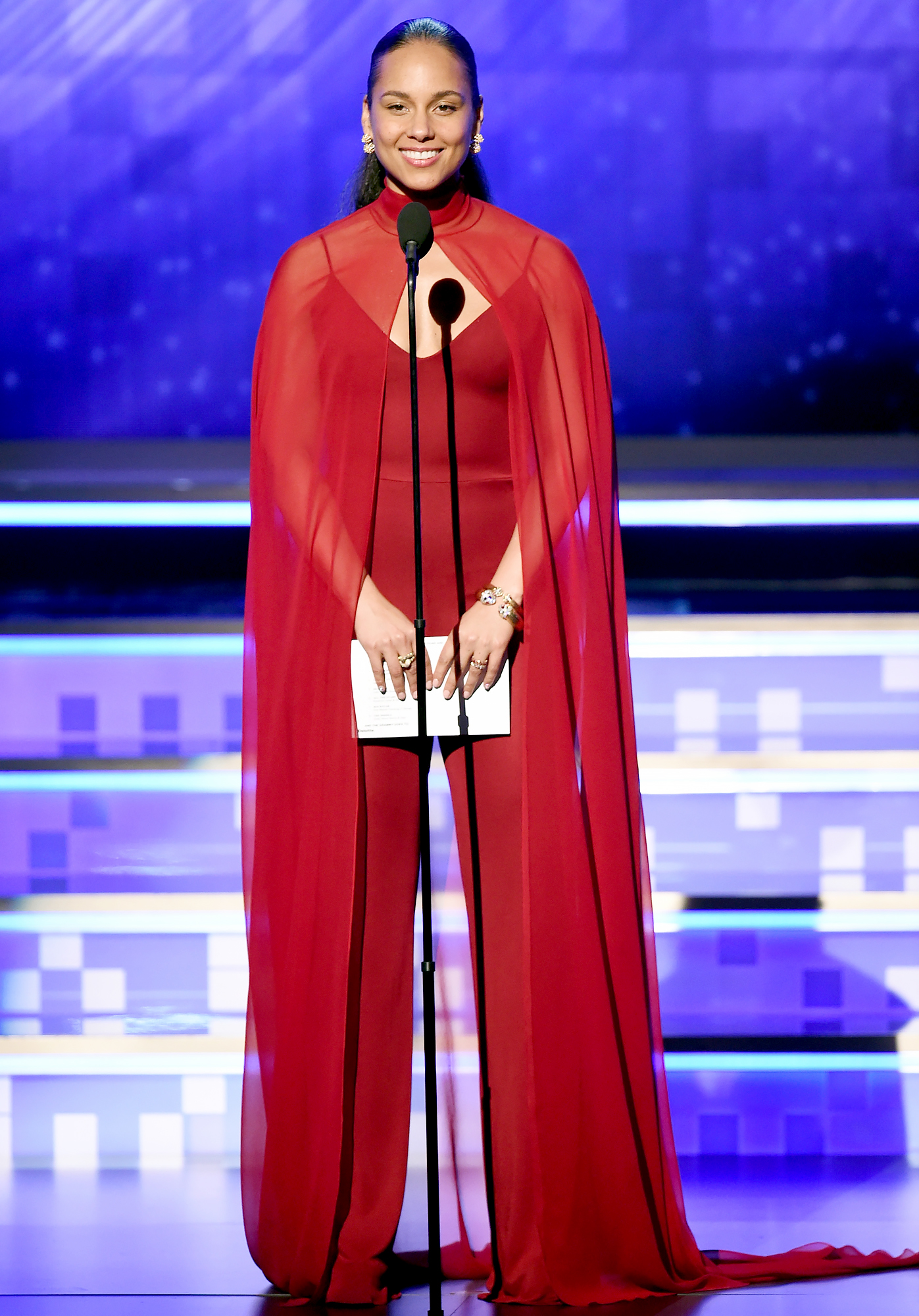 alicia-keys-grammys-2019-looks-3 - To present the night's biggest honors — Record and Album of the Year — the host was back in red. This time, she rocked a cape-like Oscar de la Renta jumpsuit with David Webb and Cartier bling.
