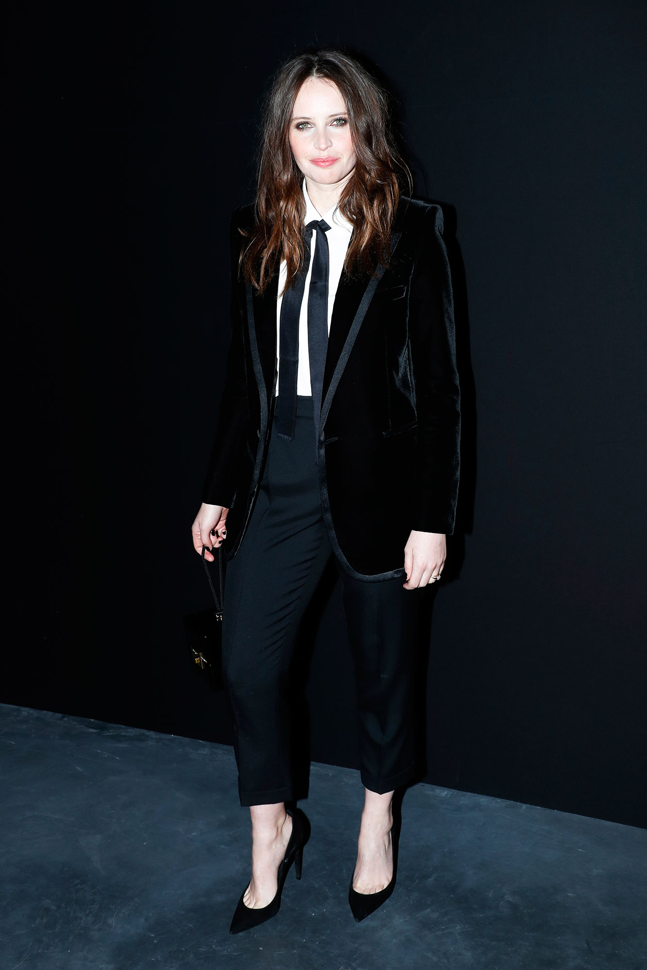 Felicity Jones See the Stars' Street Style at Paris Fashion Week - We love the menswear vibes of the British beauty's velvet blazer and black trousers combo at Saint Laurent on Tuesday, February 26.