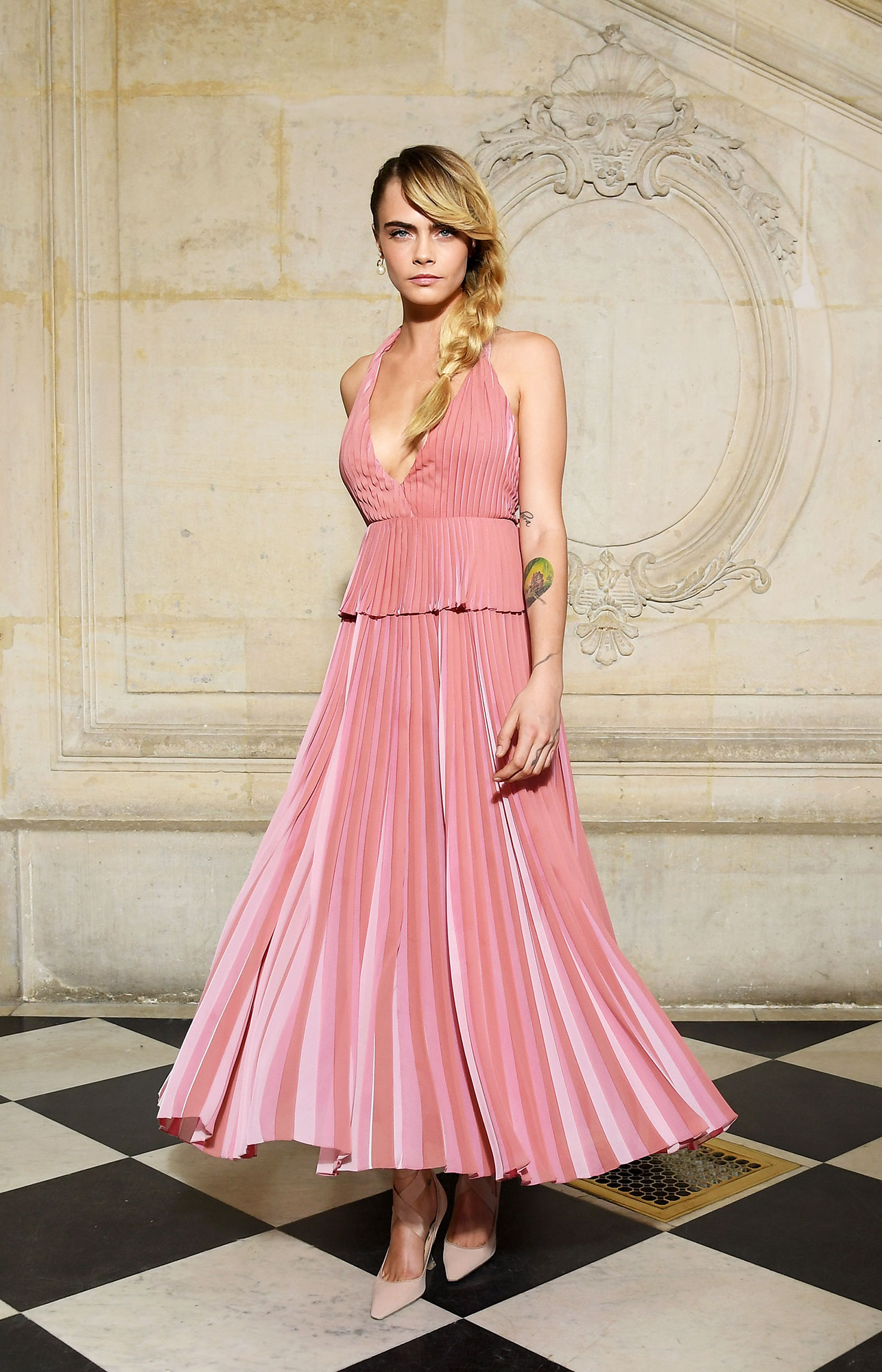 Cara Delevingne See the Stars' Street Style at Paris Fashion Week - She's thinking pink! The new face of Dior Makeup's Stellar Shine lipstick opted for a pastel pleated tea-length frock at Dior on Tuesday, February 26.