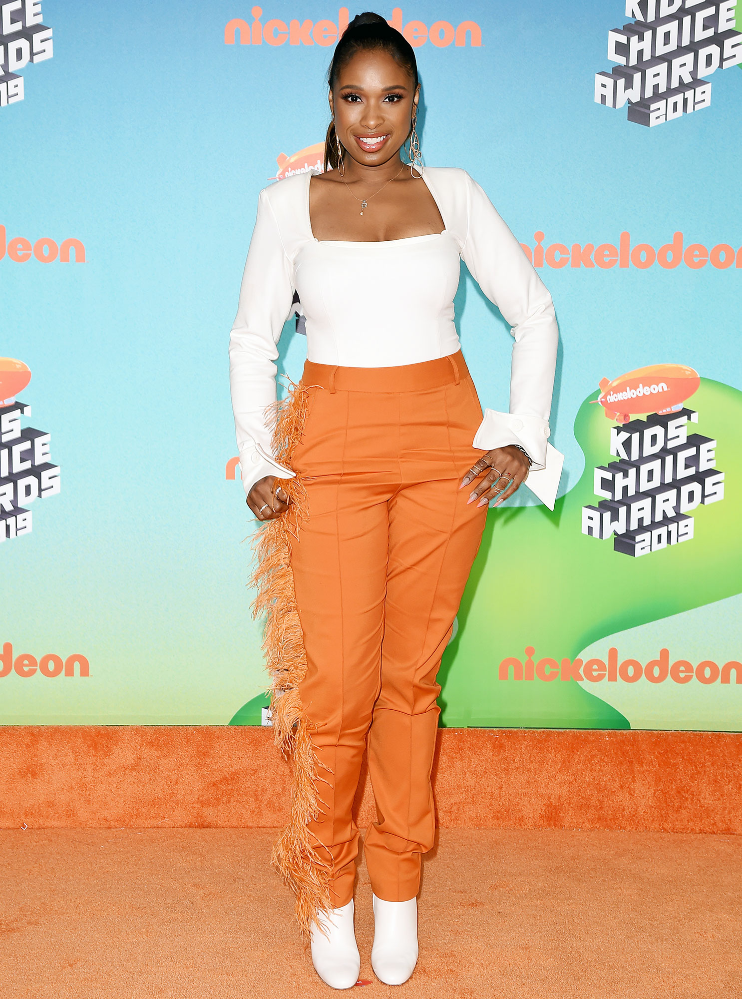 Nickelodeon Kids Choice Awards 2019 Jennifer Hudson - The 37-year-old singer wore an outfit from Hanifa that included festive orange pants with a bit of fringe along one side and a white long-sleeve top.