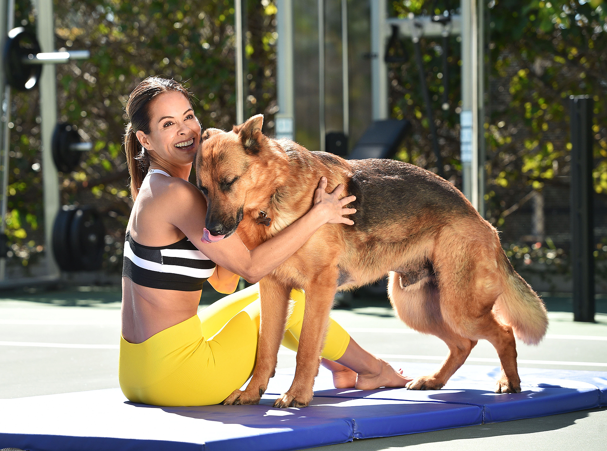 Brooke-Burke's-Go-To-Exercises-to-Do-in-the-Backyard - After your strengthening session, stretch any muscles you feel could use a little love. Feel free to rest on your back or sitting up and gather your thoughts — a furry friend never hurts!