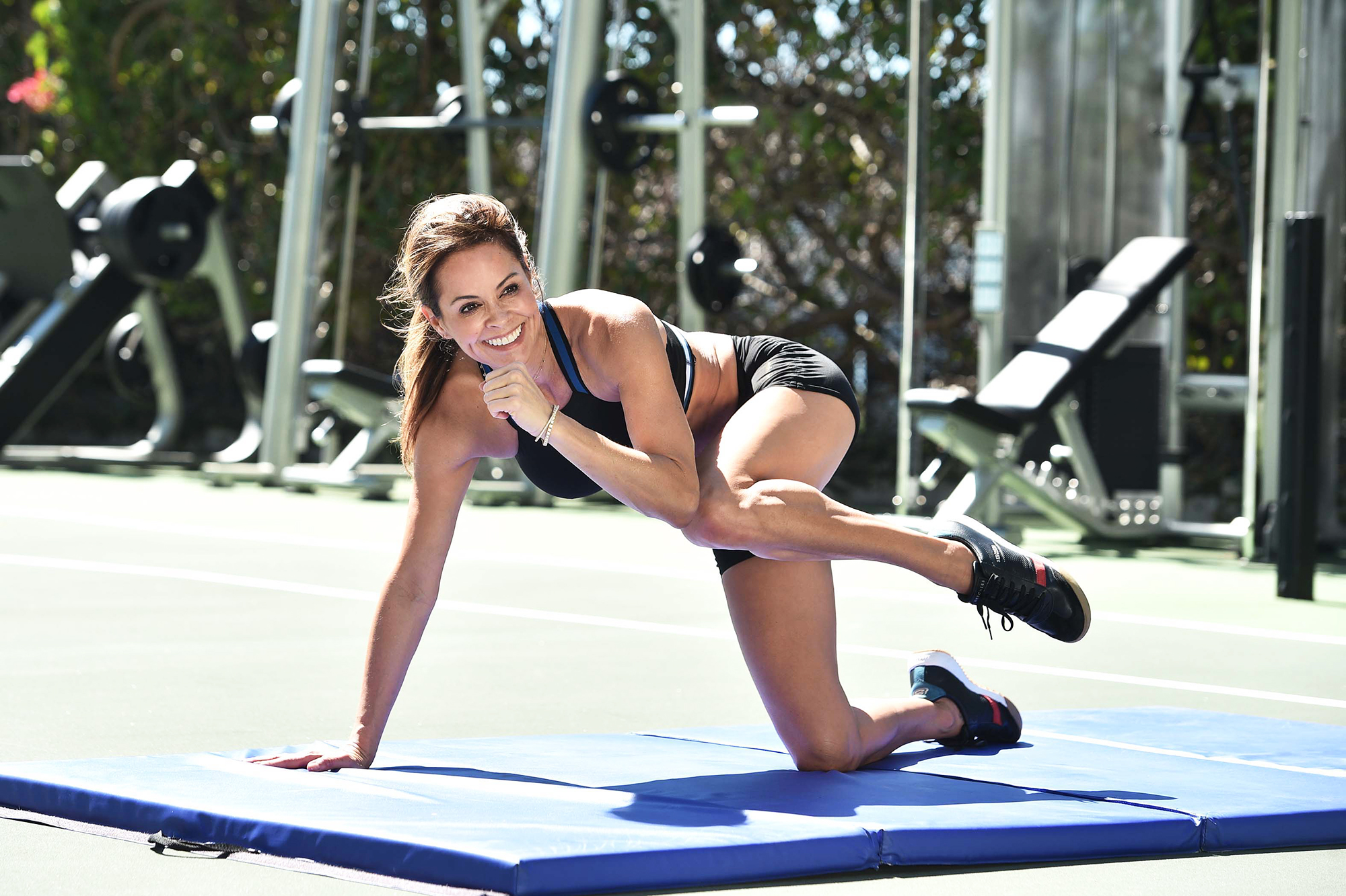 Brooke-Burke's-Go-To-Exercises-to-Do-in-the-Backyard - Start by kneeling on all fours. Stabilize your balance, then bring your left knee and left elbow together at the angle Burke demonstrates.
