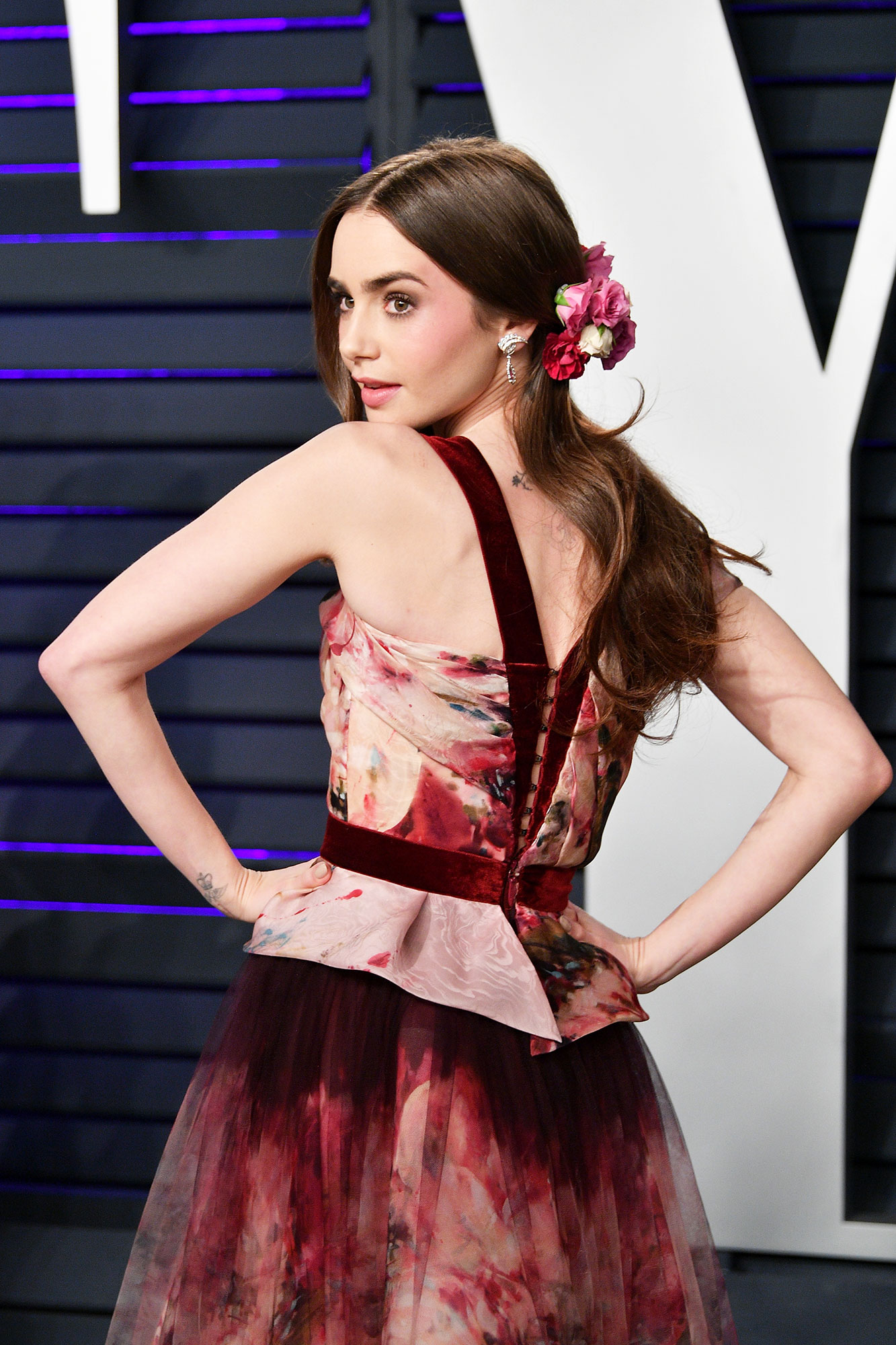 """Lily Collins Celebs Are Here With All the Coachella Beauty Inspo You Need - Celeb hair stylist Mara Roszak shared that she cut fresh rose stems down to the bud and glued them onto a plain bridal veil comb to create the brunette beaty's dreamy hair accessory at the 2019 Vanity Fair Oscar Party. """"You can play around with shapes or use a headband,"""" she shares ."""