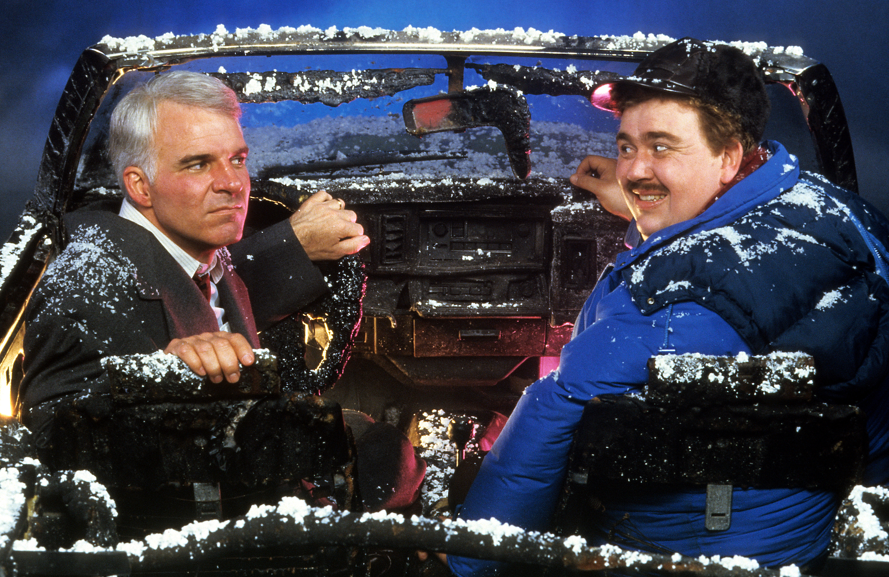 Ryan Reynolds Posts Video Tribute to John Candy on 25th Anniversary of His Death - Steve Martin and John Candy sit in a destroyed car in a scene from the film 'Planes, Trains & Automobiles', 1987.