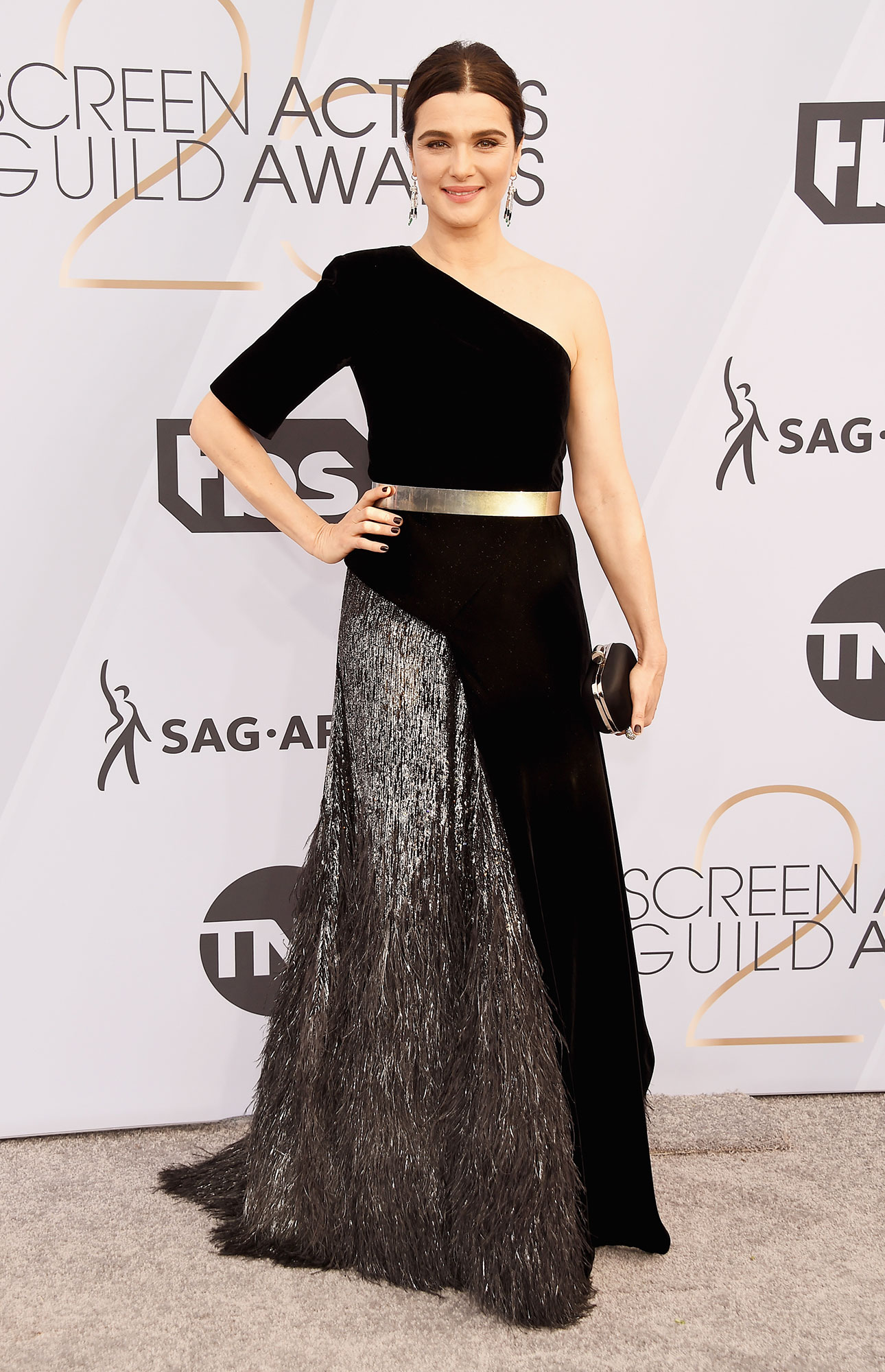 Happy Birthday, Rachel Weisz! See Her Hottest Red Carpet Looks - When attending the 2019 SAG Awards, Weisz wore a funky chic one-sleeve dress with silver feathers on one side of the skirt with a shiny belt around her waist.