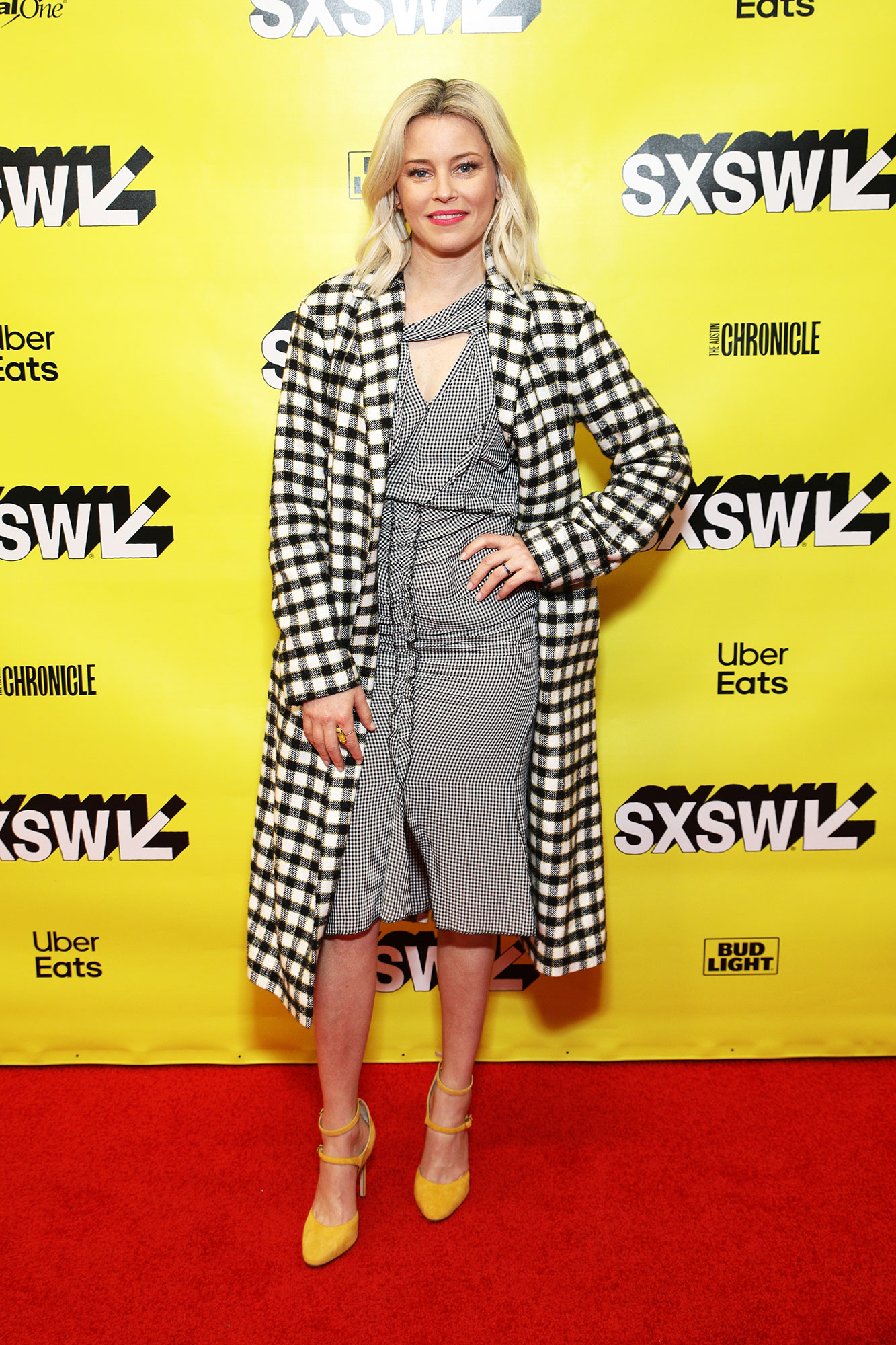 SXSW Is Giving Us Chic Outfit Inspo for Spring - Showing Us all that she's not afraid to mix prints on Monday, March 11, the Pitch Perfect director paired her black and white gingham dress with a larger check coat and yellow heels.