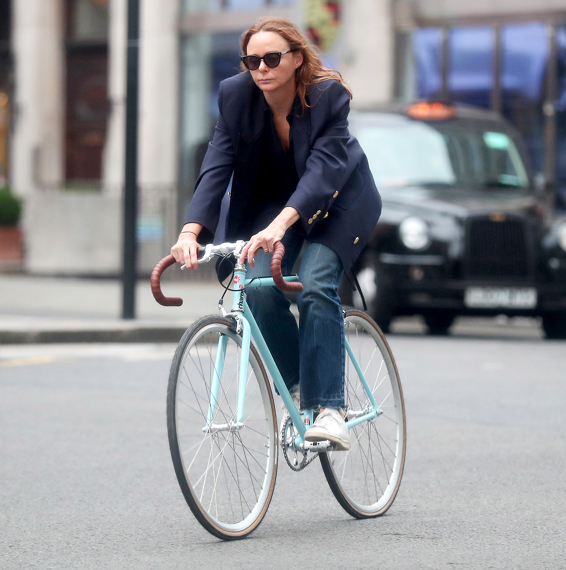 Stella-McCartney-biking - The fashion designer went for a chic ride in an oversized blazer and jeans in London on June 12, 2018.