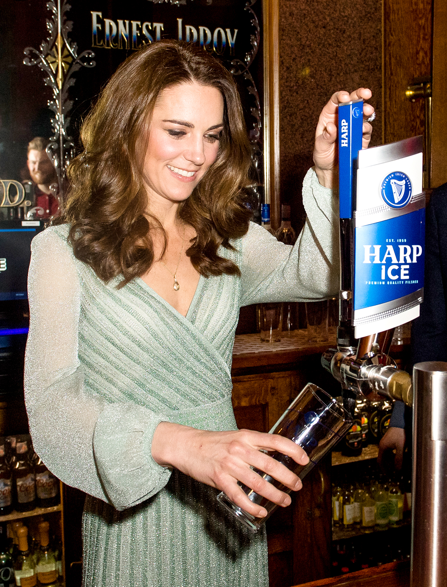 Stepping-Behind-the-Bar-duchess-kate - The Duchess of Cambridge opted to serve a beer instead of sip one during a visit to Empire Music Hall Belfast in Belfast, Northern Ireland. Believe it or not, the mother of three pulled a pint without getting any beer on her glittery green Missoni dress on February 27, 2019.