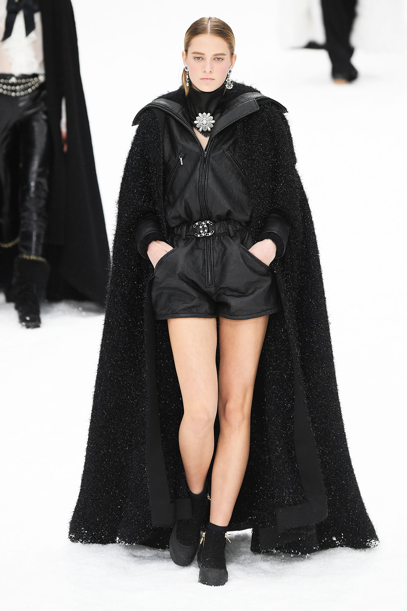 "Karl Lagerfeld's Final Runway Was a Star-Studded Tribute to the Late Designer - For a bit of edge, this long black cape was the perfect addition to a short jumper secured at the waist with a double ""C""-logo belt."