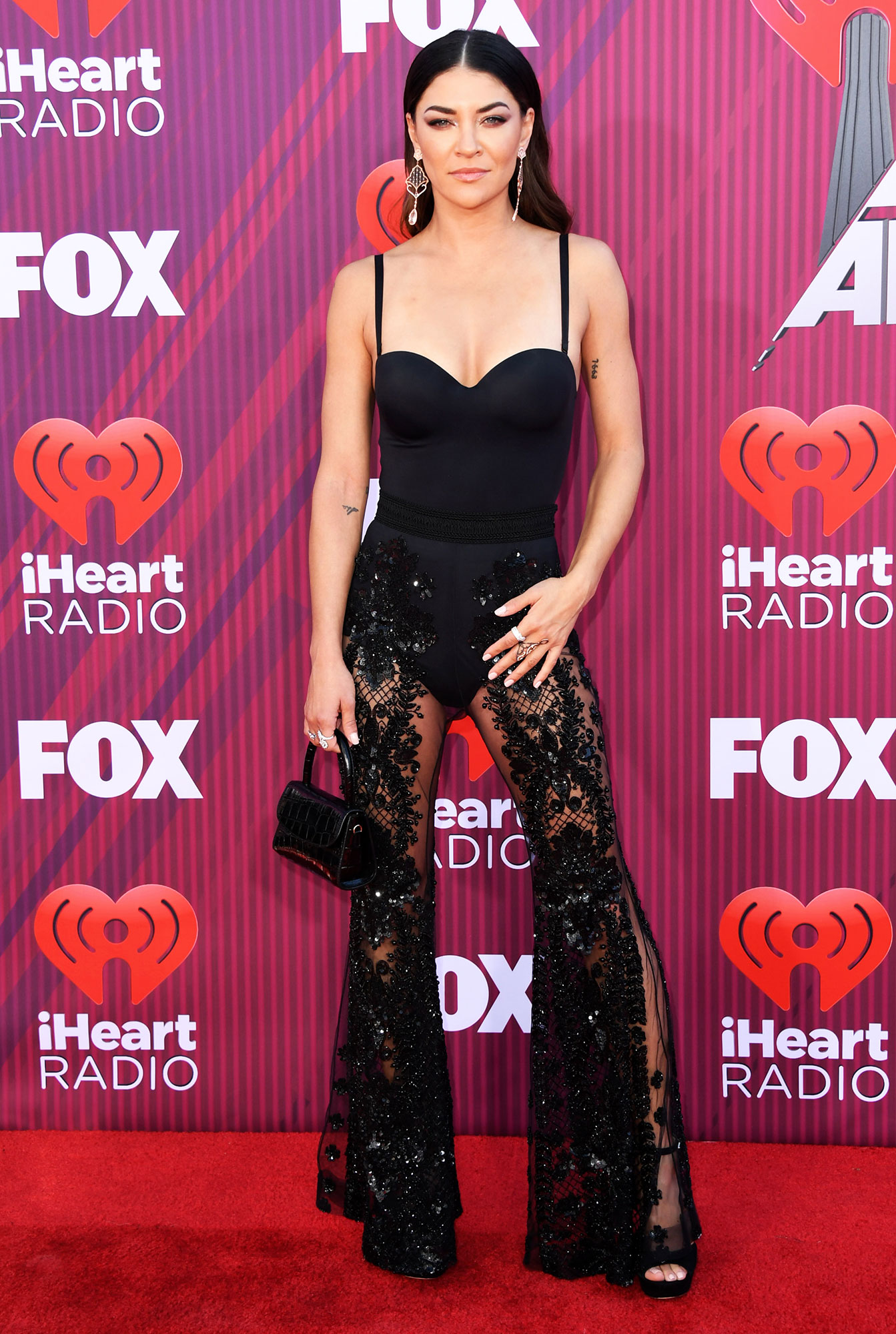 Jessica Szohr See What the Stars Wore to the iHeart Radio Music Awards 2019 - Wearing a black nearly naked lace jumpsuit and Hearts On Fire jewelry.