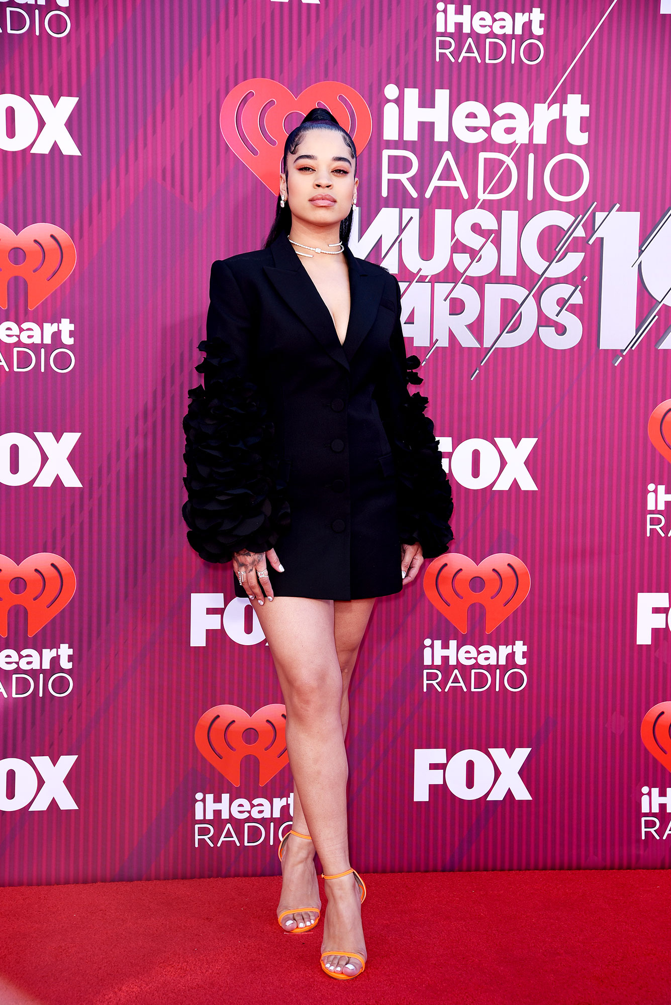 Ella Mai See What the Stars Wore to the iHeart Radio Music Awards 2019 - Wearing a blazer-inspired black Acler mini with orange heels.