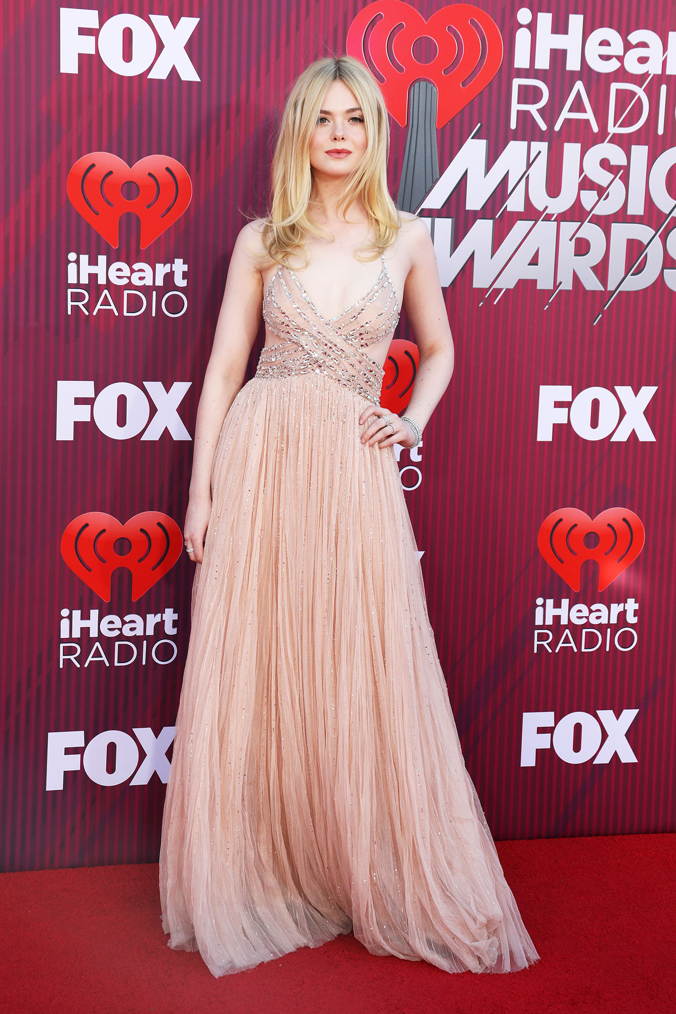 Elle Fanning See What the Stars Wore to the iHeart Radio Music Awards 2019 - Wearing a blush pink Miu Miu tulle gown with crystal embroidery.