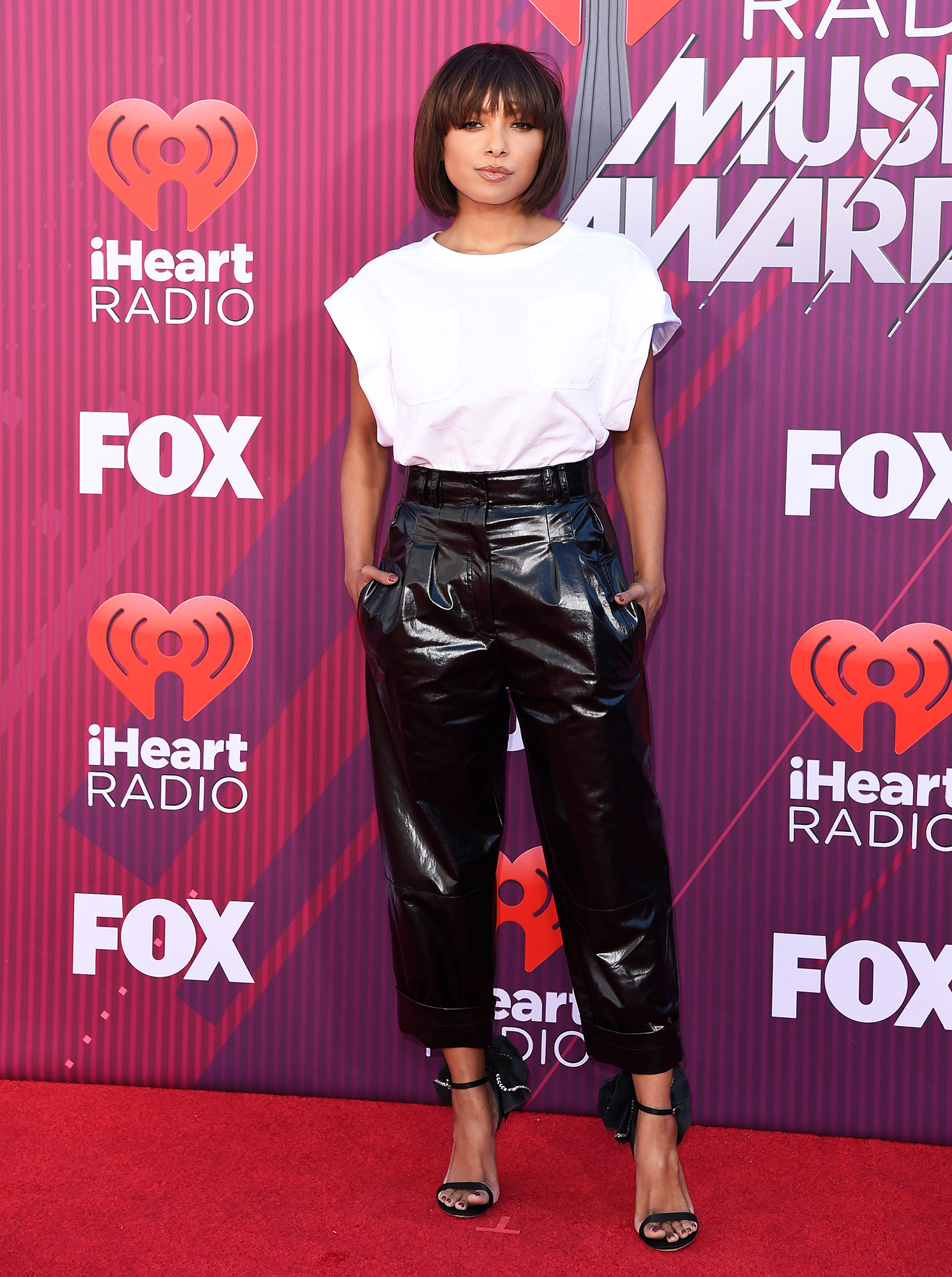 Kat Graham See What the Stars Wore to the iHeart Radio Music Awards 2019 - Wearing a white Alberta Ferretti tops with Philosophy di Lorenzo Serafini leather pants, Giuseppe Zanotti heels and AUrate and Hearts On Fire jewels.