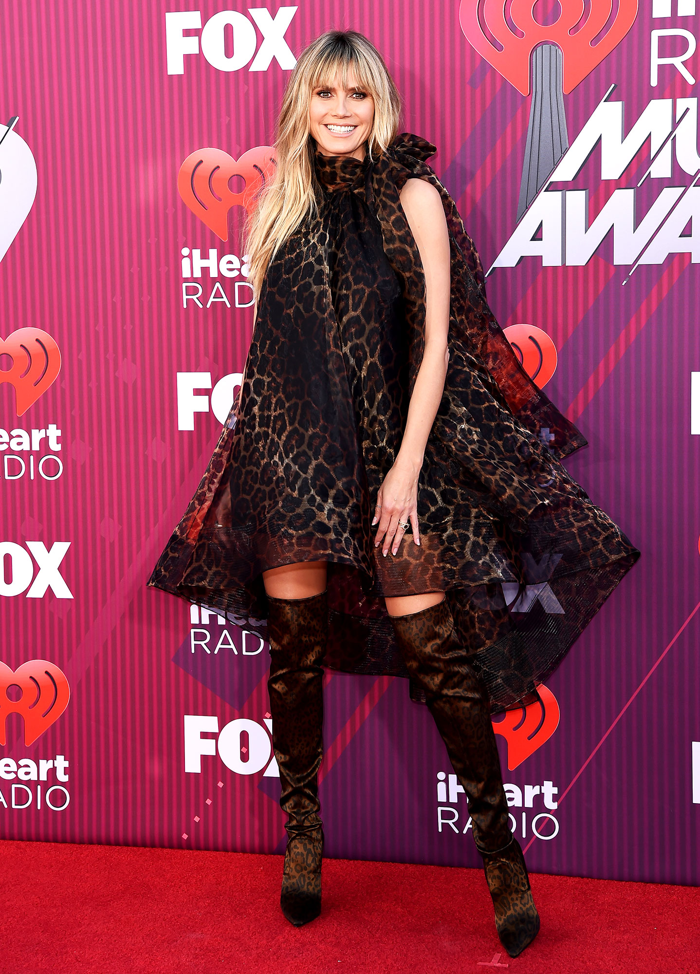 Heidi Klum See What the Stars Wore to the iHeart Radio Music Awards 2019 - Wearing an animal print Christian Siriano mini with matching Le Silla boots, Lorraine Schwartz jewels and a Tyler Ellis clutch.