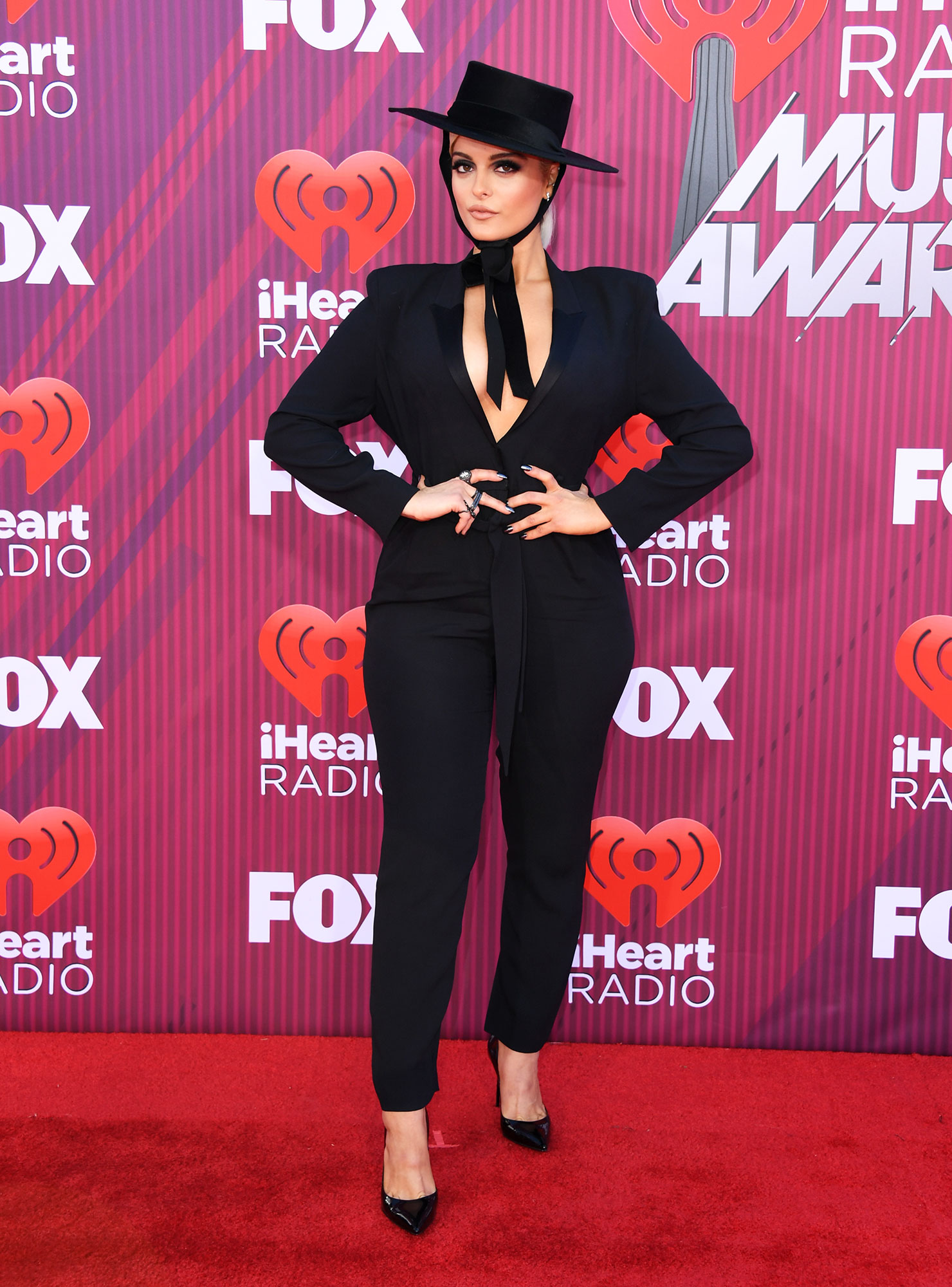 Bebe Rexha See What the Stars Wore to the iHeart Radio Music Awards 2019 - Wearing a shirtless black tux with a wide-brim hat.