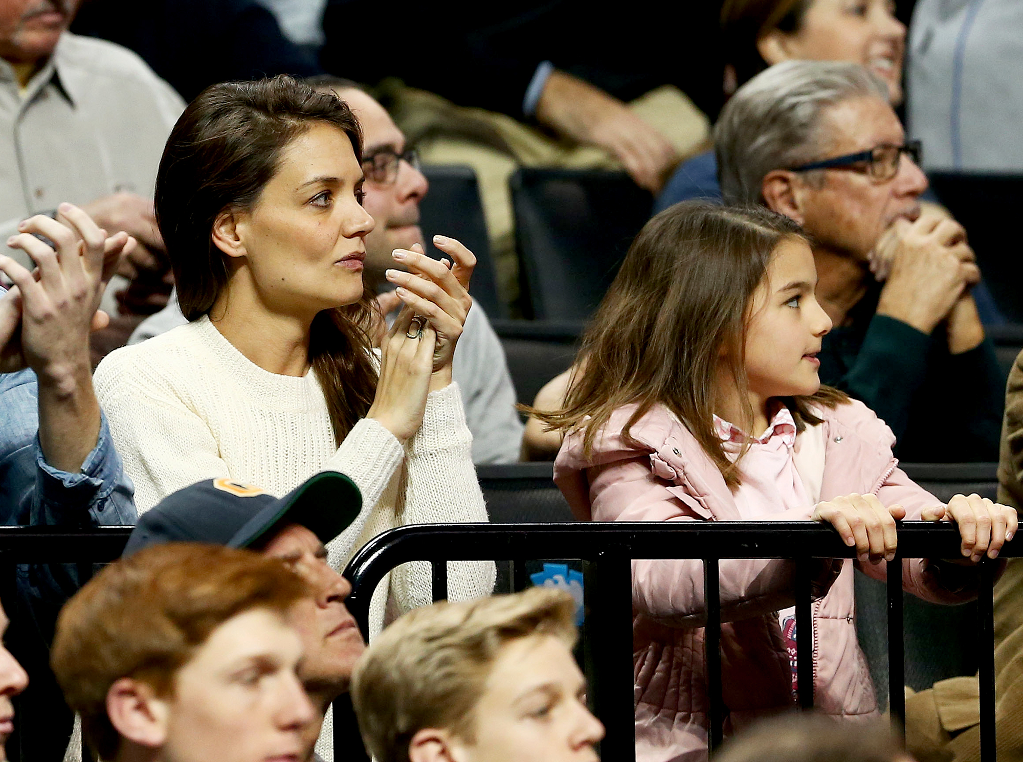 katie-holmes-suri-cruiseSports-Fan - Suri looked pretty in pink as she watched a Notre Dame basketball game inside Brooklyn's Barclays Center with her mother in March 2016.