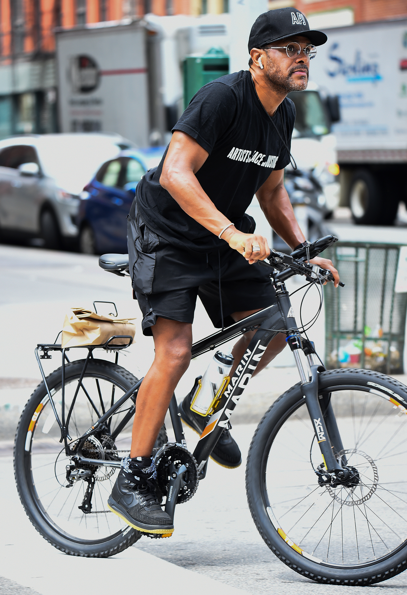 maxwell-biking - With a water bottle in tow and a package strapped to the back of his bike, the singer cycled through downtown NYC on August 2, 2018.