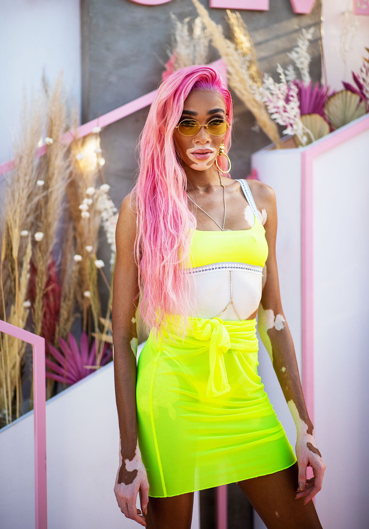 Winnie Harlow coachella 2019 hair makeup beauty - The Canadian model went all in on bright colors, wearing a neon miniskirt and crop top with brilliant pink strands that reached down to her waist.