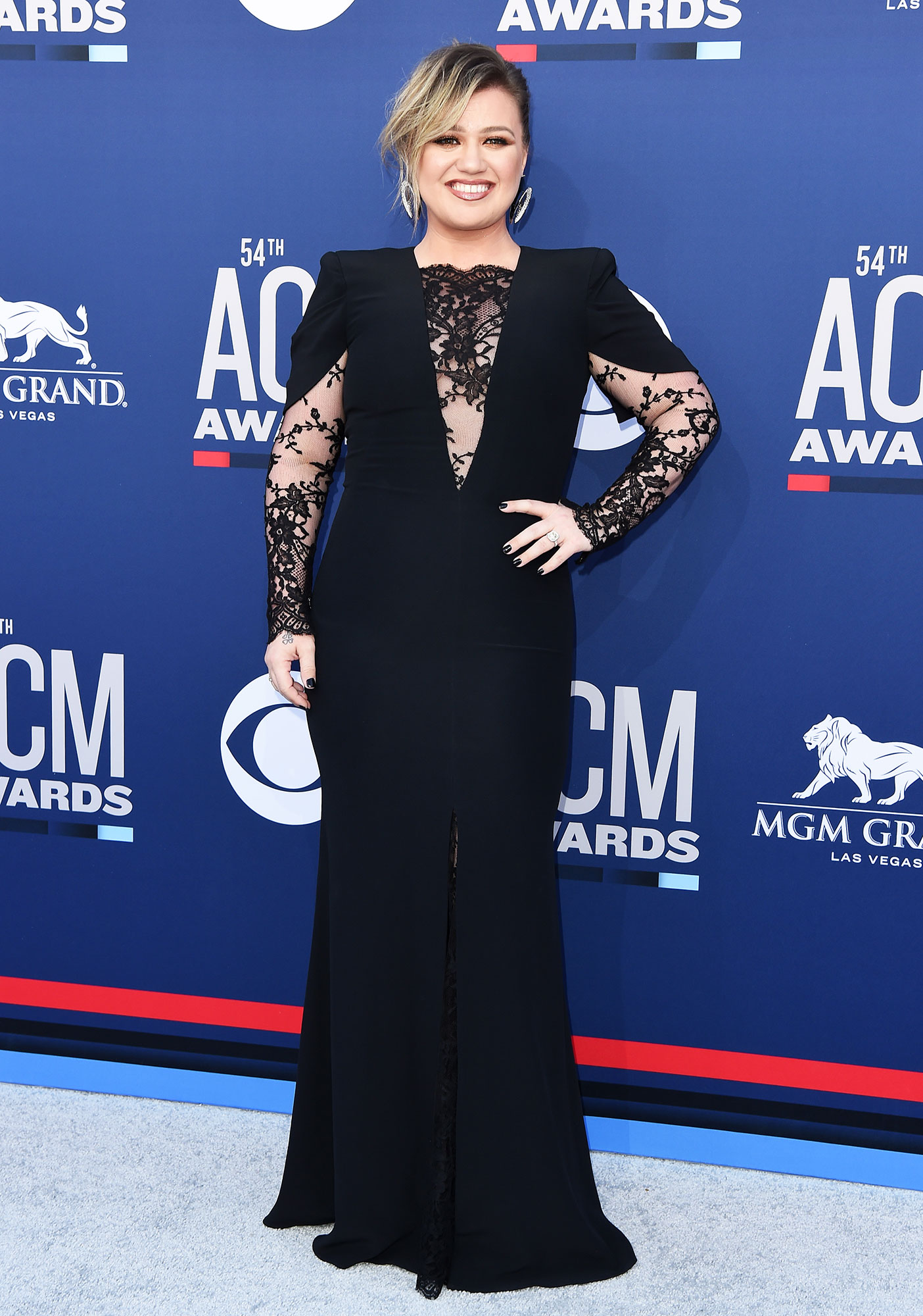 """Kelly Clarkson The Best Looks From the Country Music Awards Red Carpet - Giving Us a bit of edge, the """"Because of You"""" singer looked gorgeous in a black ballgown with lace details on the sleeves and neckline."""