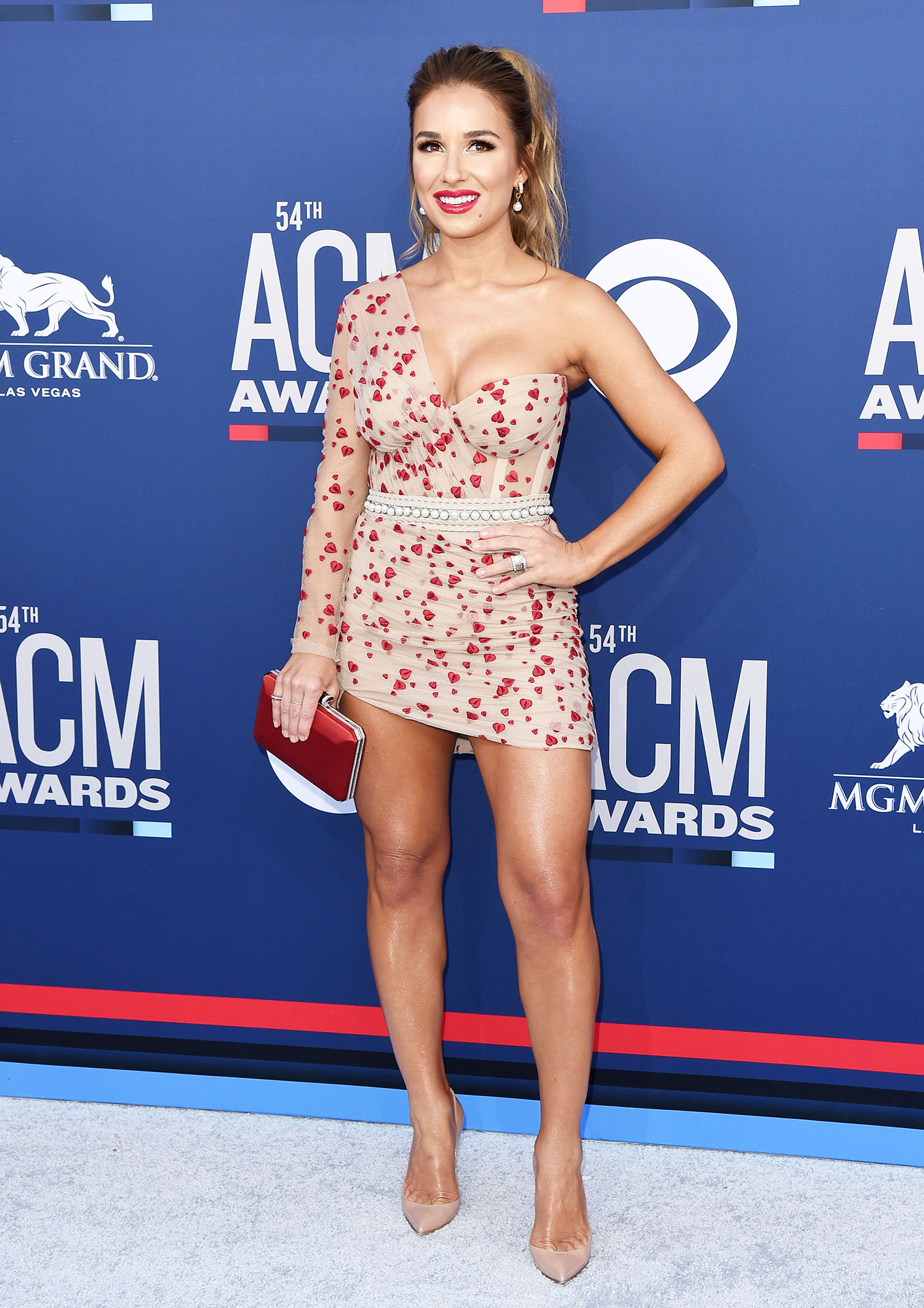 """Jessie James Decker The Best Looks From the Country Music Awards Red Carpet - The """"Lights Down Low"""" singer looked super sexy in a nude and red one-sleeve minidress."""