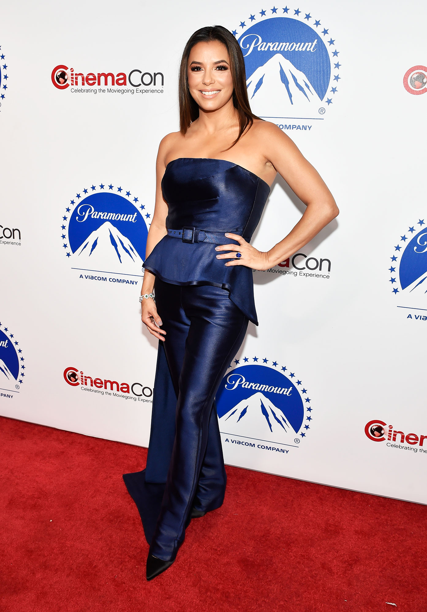 Eva Longoria The Stars Are Bringing Their Style A-Game to CinemaCon - Still basking in that new mom glow, the multi-hyphenate served up boss-lady vibes in a Vitor Zerbinato jumpsuit, Victoria Beckham pumps and Nigora Tabayer jewels on Thursday, April 4.