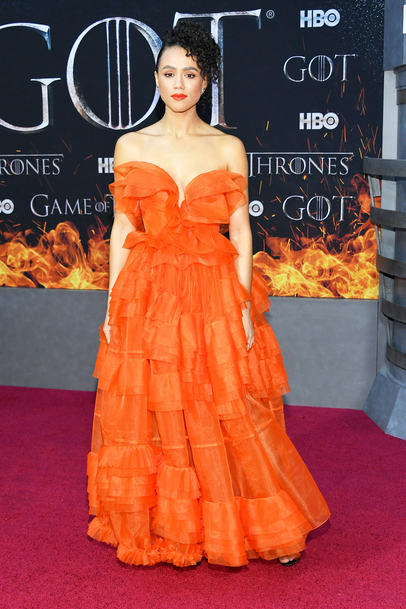 Nathalie Emmanuel game of thrones - Wearing a voluminous orange Ermanno Scervino gown and Jimmy Choo sandals.