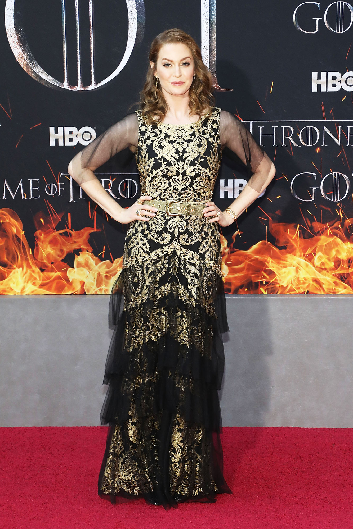 Esme Bianco game of thrones - Wearing an ornate black and gold belted gown with tulle sleeves.