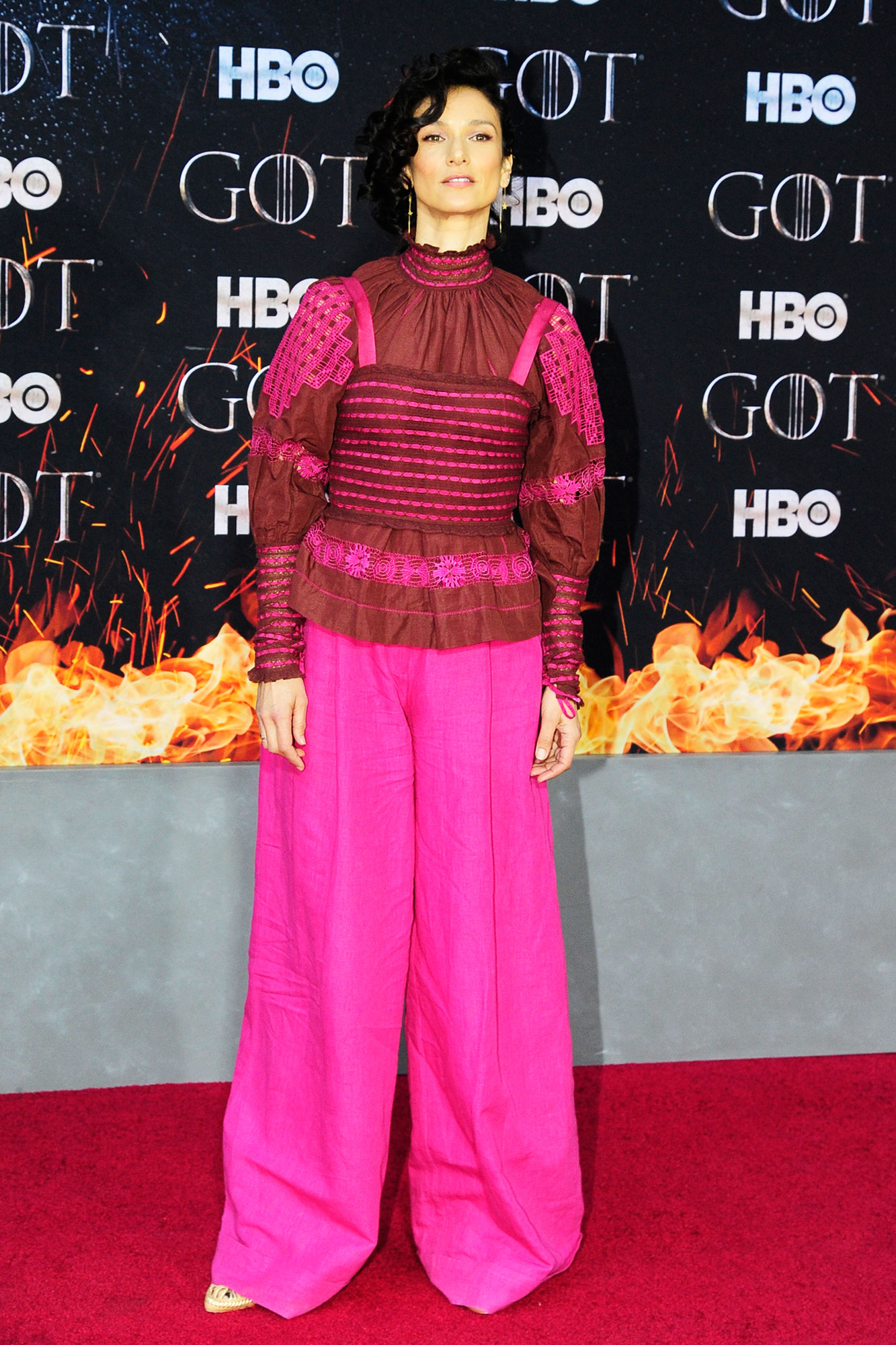 Indira Varma game of thrones - Wearing pink wide-leg trousers with a embroidered mock-neck blouse.