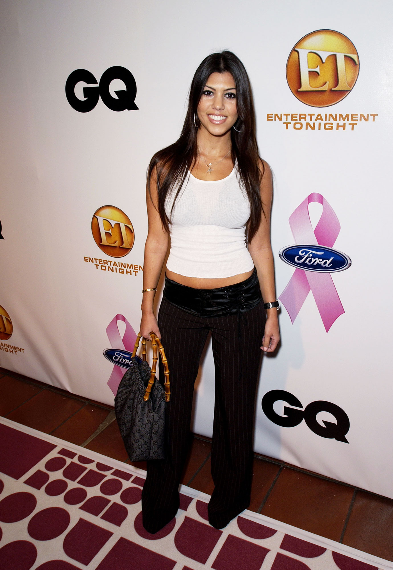 Happy 40th Birthday, Kourtney Kardashian - It doesn't get much more #TBT than the low-slung pants and a wife-beater the Keeping Up With the Kardashians star sported on one of her first red carpets.