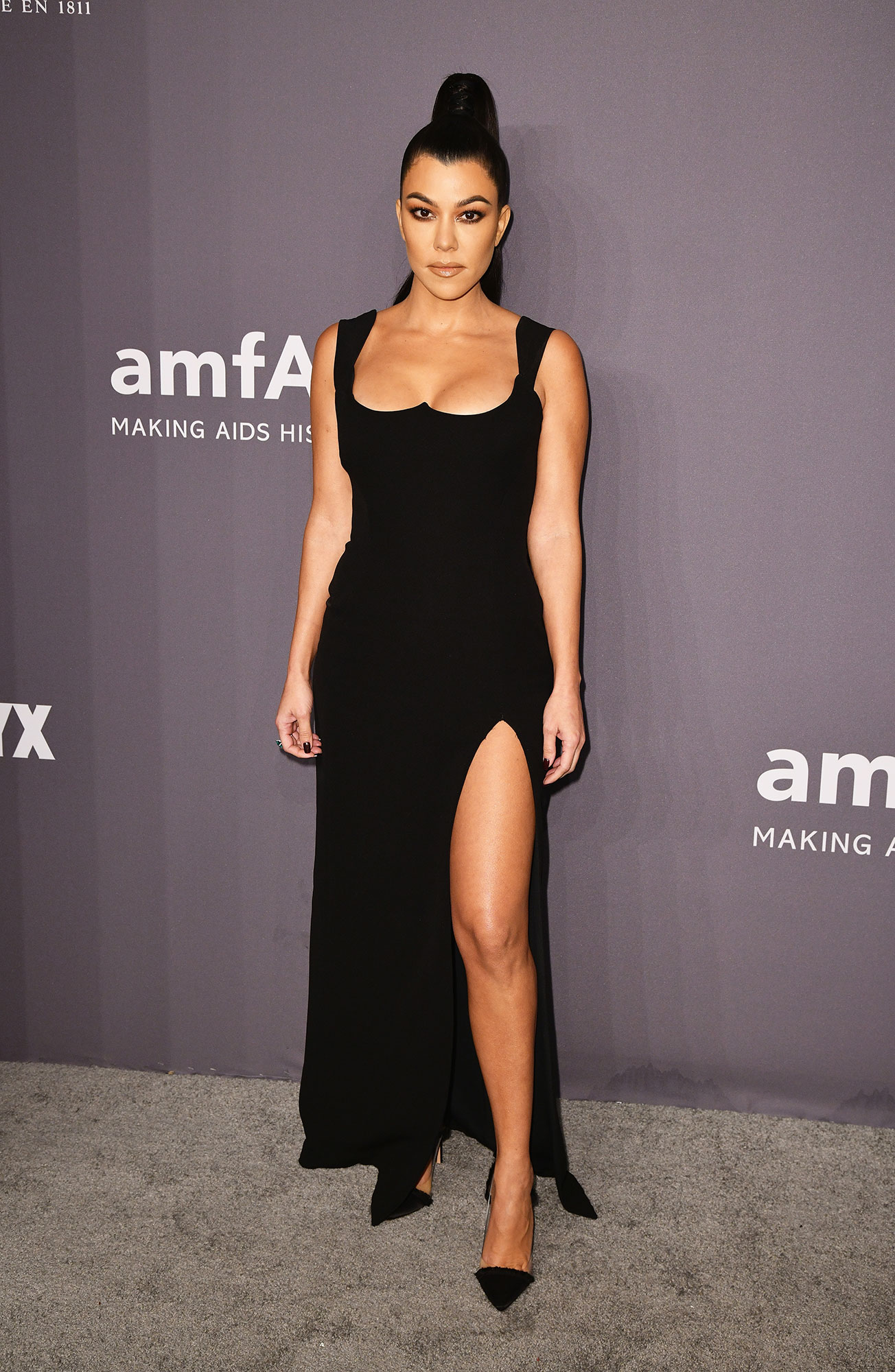 Happy 40th Birthday, Kourtney Kardashian - Giving black tie dressing a sexy spin, the Poosh founder rocked a slitted Versace gown and Gianvito Rossi pumps at the 2019 amfAR New York Gala.