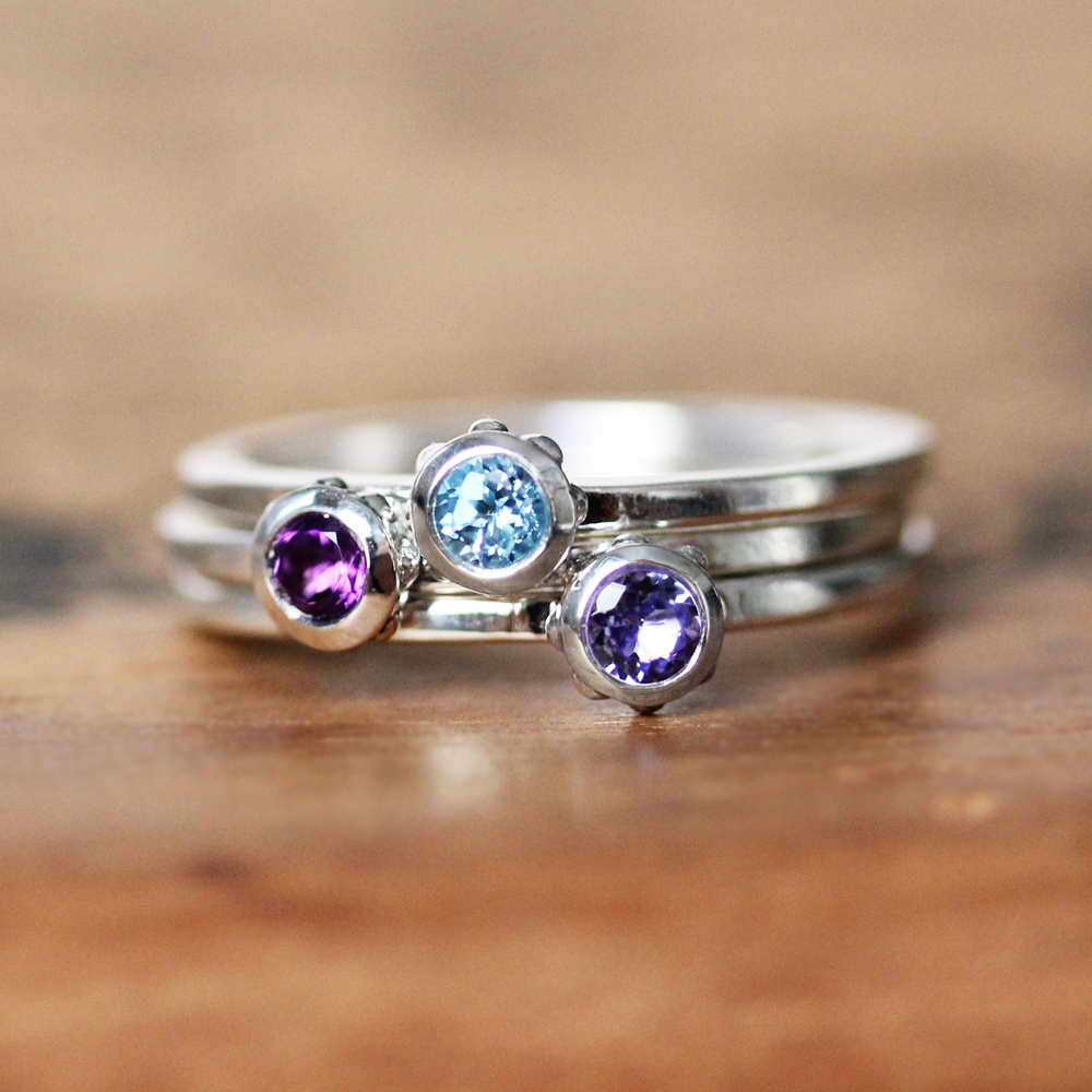 Metalicious-Birthstone-Stacking-Rings - Layer up with one piece of jewelry to honor each child! These wrought bezel rings feature tiny birthstone beads.