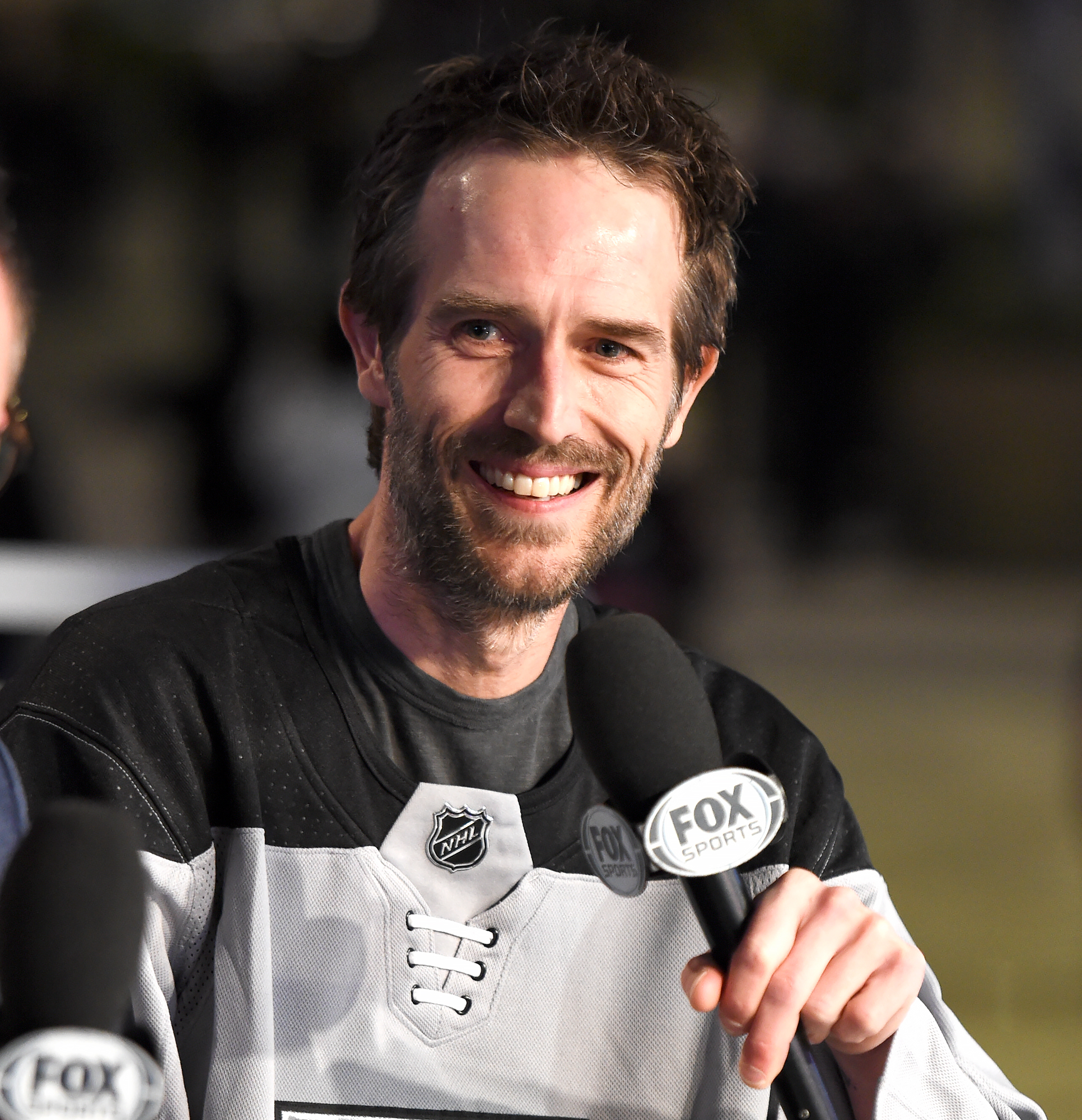"""Michael-Vartan-2019 - Michael Vartan smiles while serving as Celebrity Guest of Honor on the Los Angeles Kings' """"Hockey Night in L.A."""" broadcast before the game between the Boston Bruins and the Los Angeles Kings at STAPLES Center on February 16, 2019 in Los Angeles, California."""