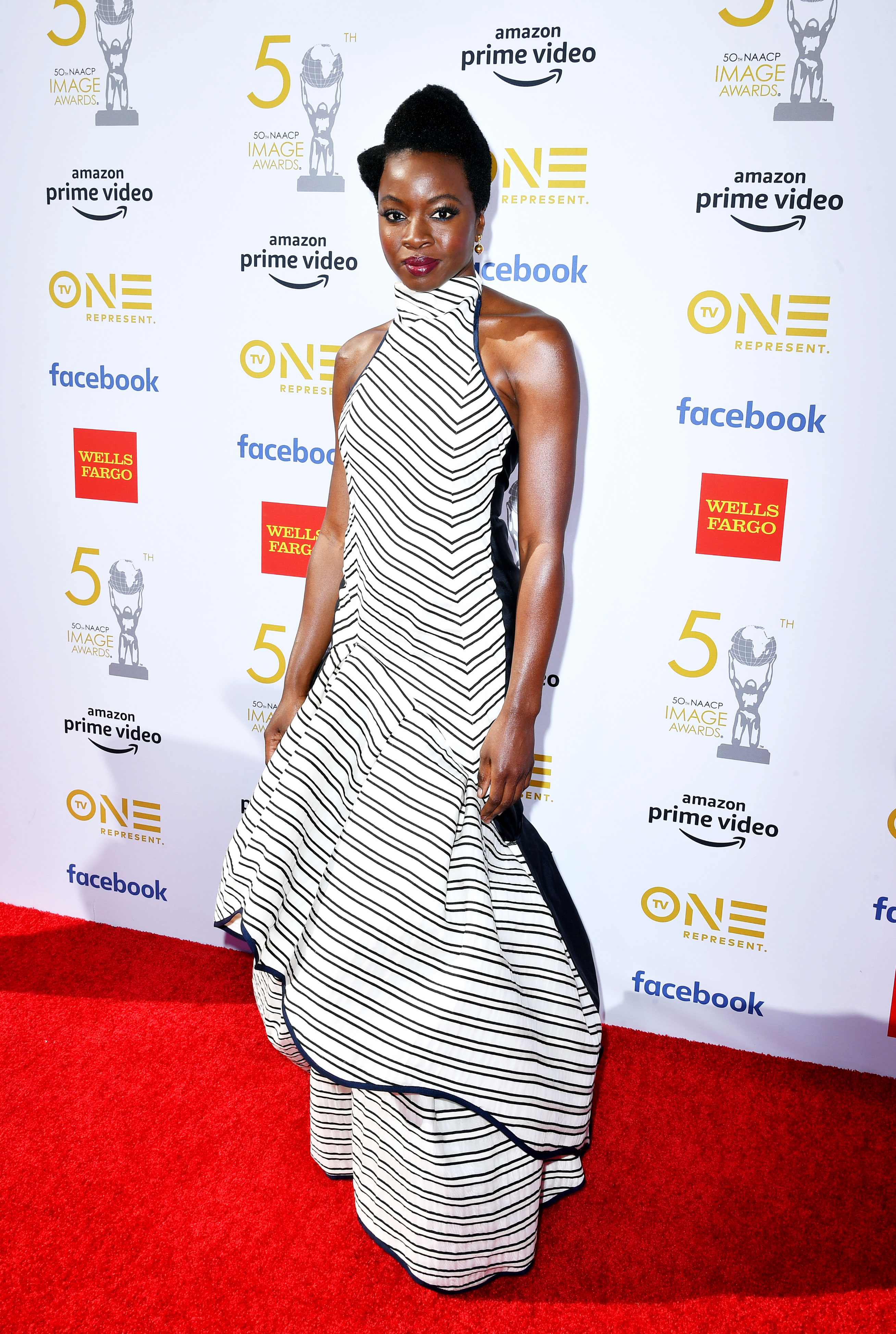Danai Gurira See the Stars at the NAACP Image Awards - Wearing a black and white striped mock-neck Rosie Assoulin gown with an asymmetrical hem.