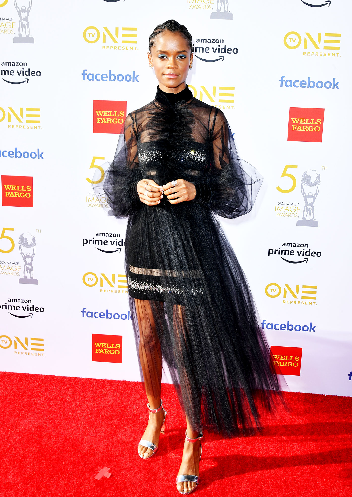 Letitia Wright See the Stars at the NAACP Image Awards - Wearing a crystal-embellished black tulle Georges Chakra mini with Nicholas Kirkwood sandals and Cartier jewels.