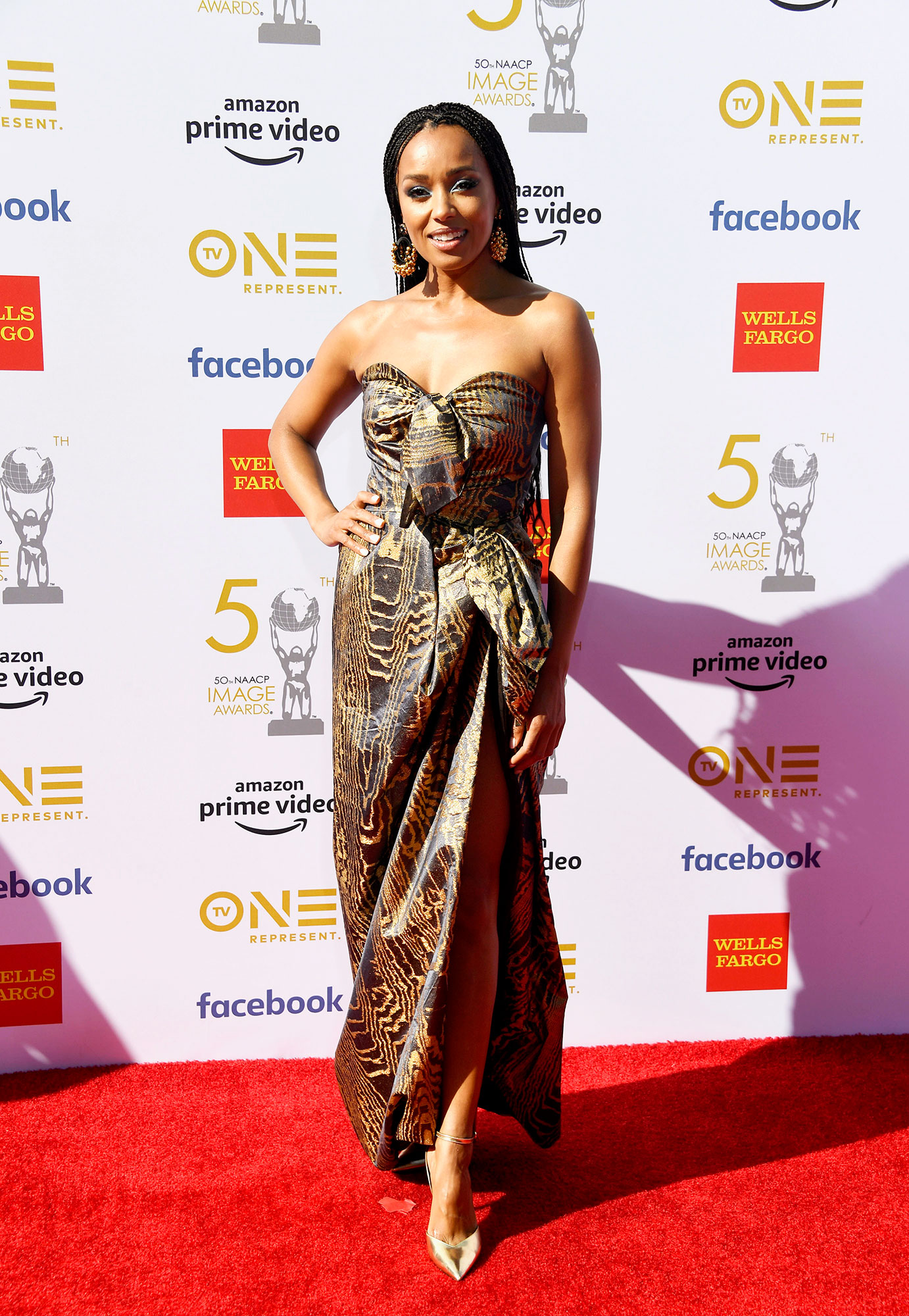 Melanie Liburd See the Stars at the NAACP Image Awards - Wearing a strapless Oscar de la Renta gown with a thigh-high slit and Stella Luna metallic pumps.