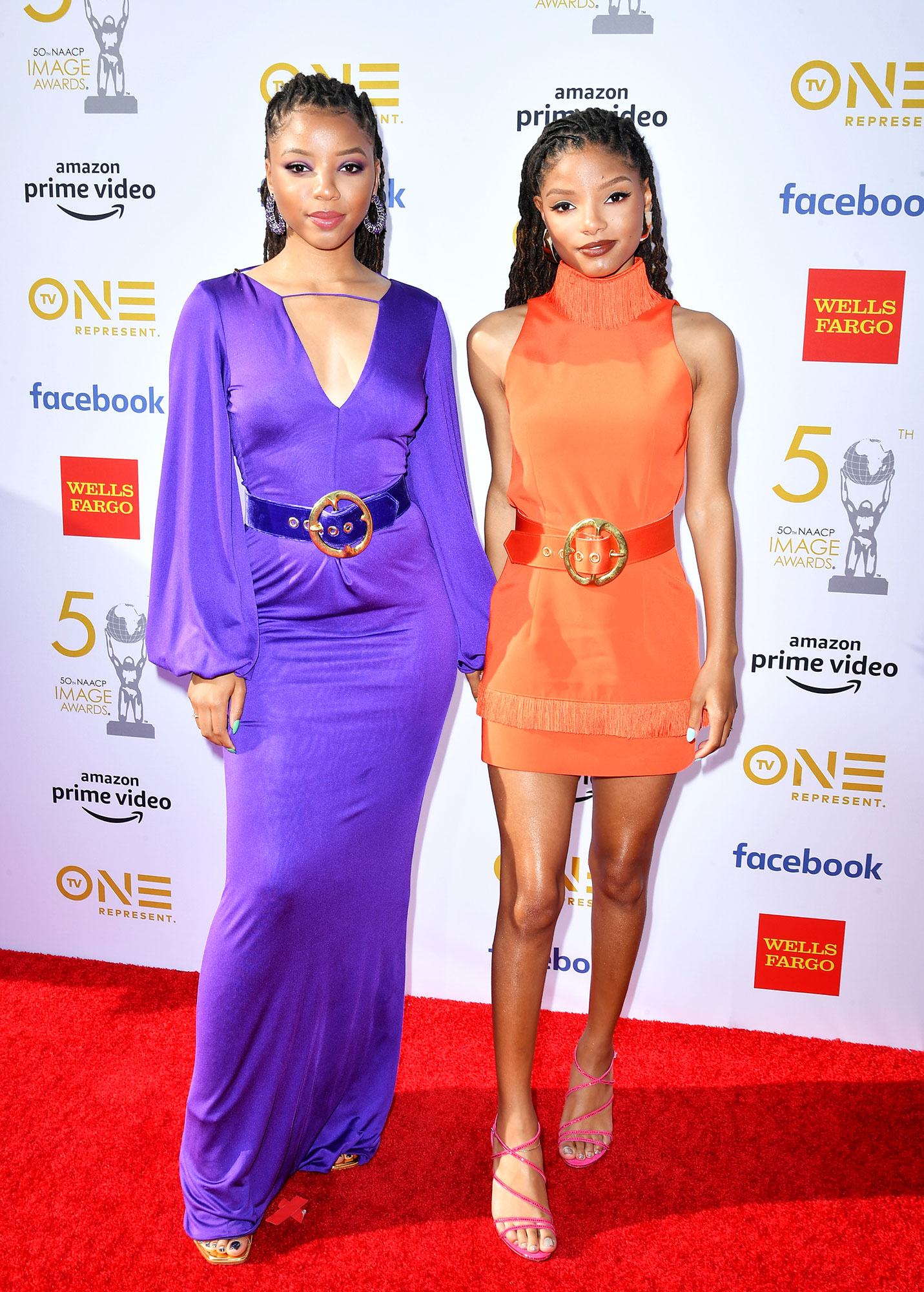 Chloe Bailey and Halle Bailey of Chloe x Halle See the Stars at the NAACP Image Awards - Wearing a purple belted maxi dress and orange mini respectively. Halle accessorized with AUrate earrings.