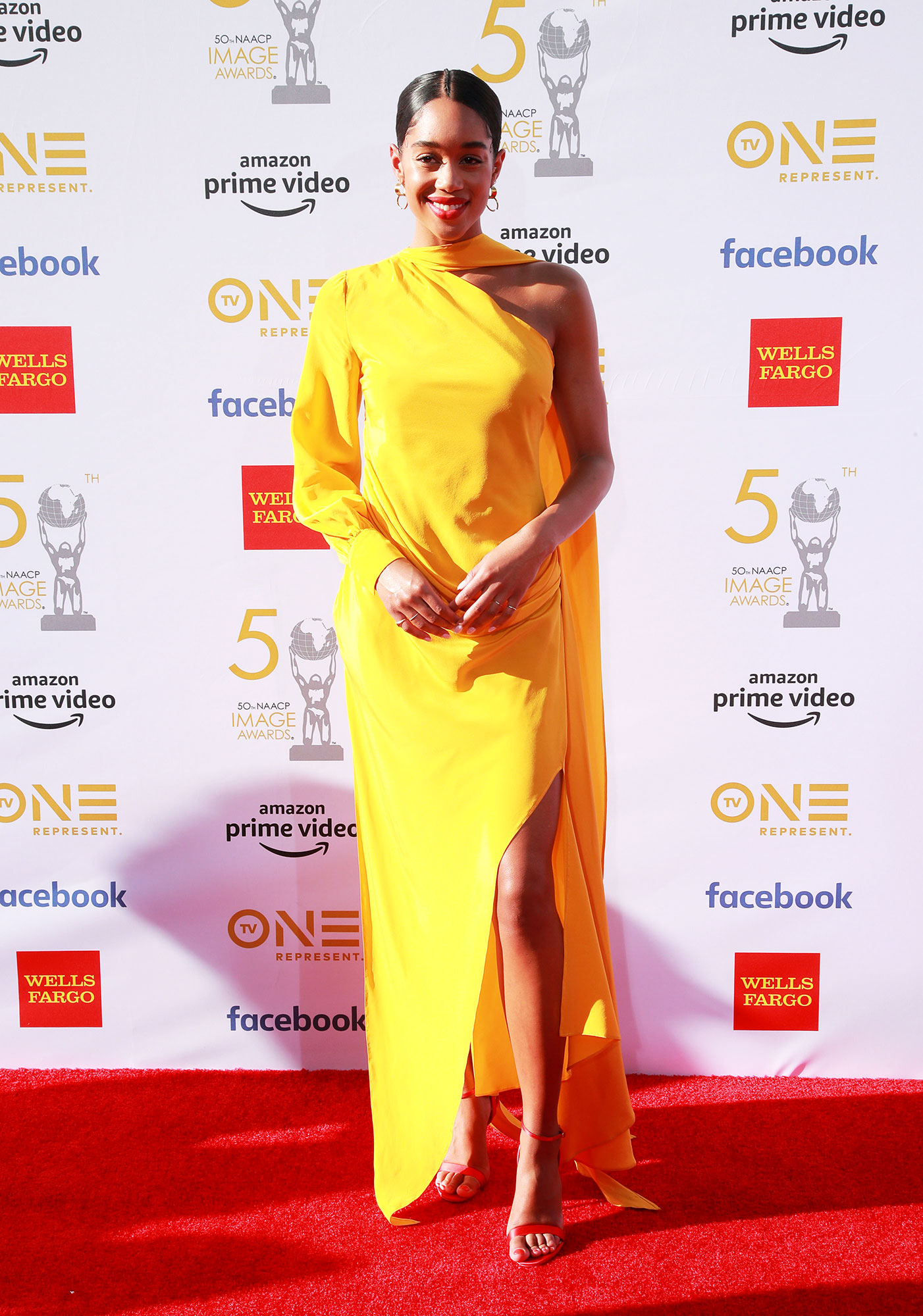 Laura Harrier See the Stars at the NAACP Image Awards - Wearing a one-shoulder yellow Pyer Moss frock with strappy sandals.