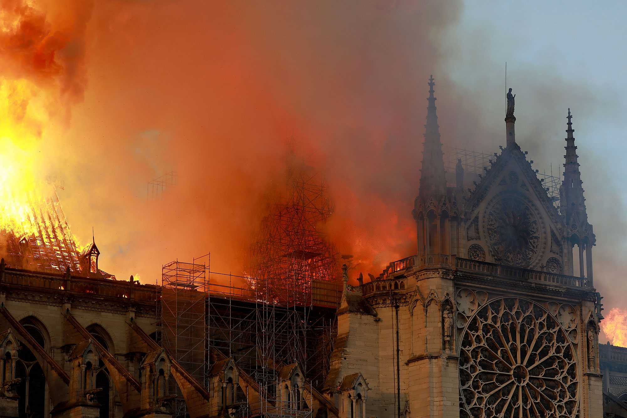 Notre Dame on Fire d - Flames and smoke are seen billowing from the roof at Notre-Dame Cathedral April 15, 2019 in Paris, France.