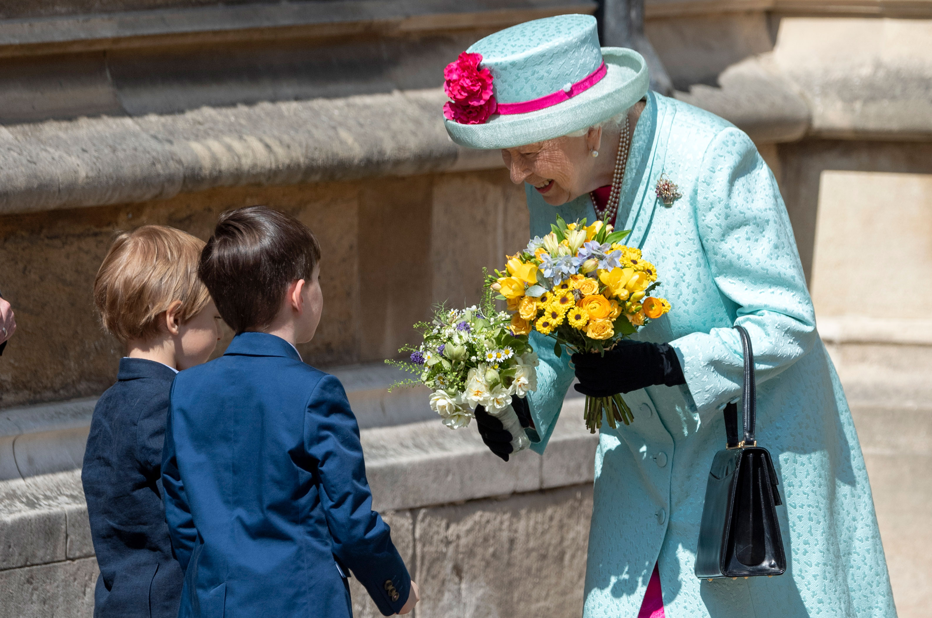 Queen Elizabeth II Royal Family Celebrate Easter - The queen bent down to interact with two children.