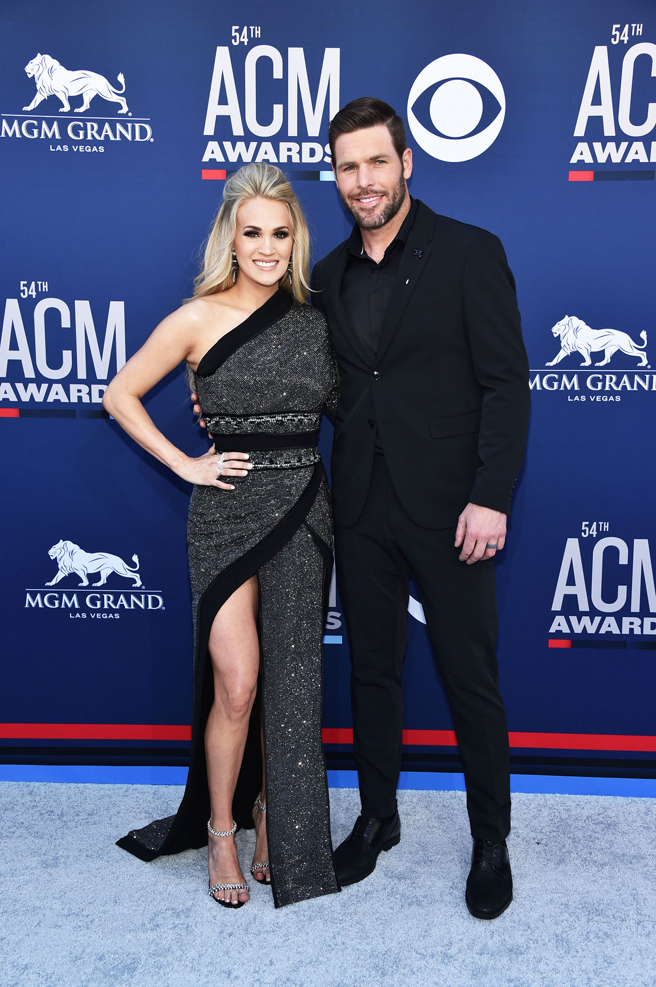 "Carrie Underwood and Mike Fisher Smoking Hot Couples Style at the ACMs - The ""Love Wins"" singer shimmered in a one-shoulder Nicolas Jebran gown and Dena Kemp jewels, while Fisher complemented her in black."
