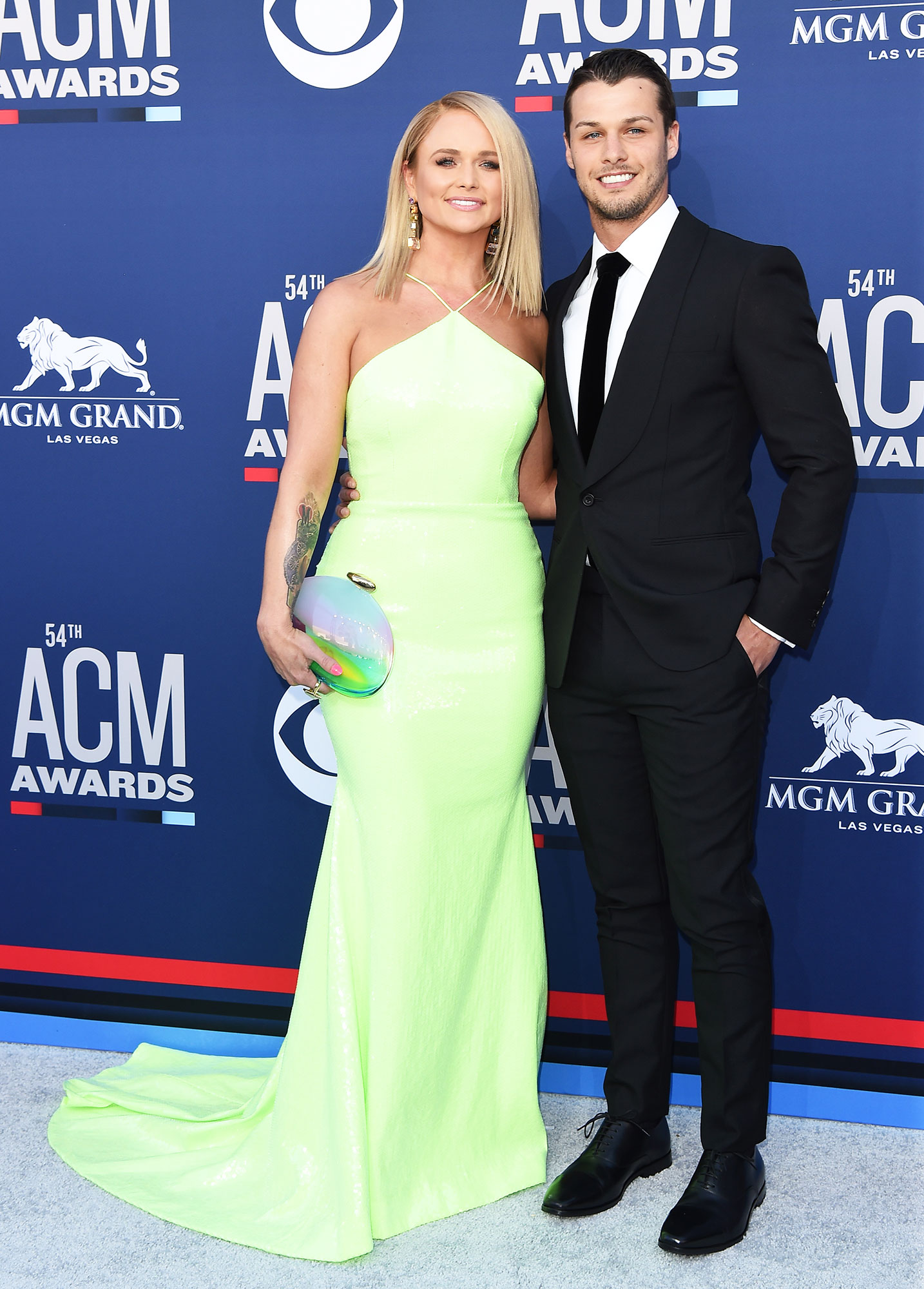 Miranda Lambert and Brendan McLoughlin Smoking Hot Couples Style at the ACMs - For their first red carpet appearance together, McLoughlin kept things classic in a black suit and Lambert brightened things up in a neon green gown.