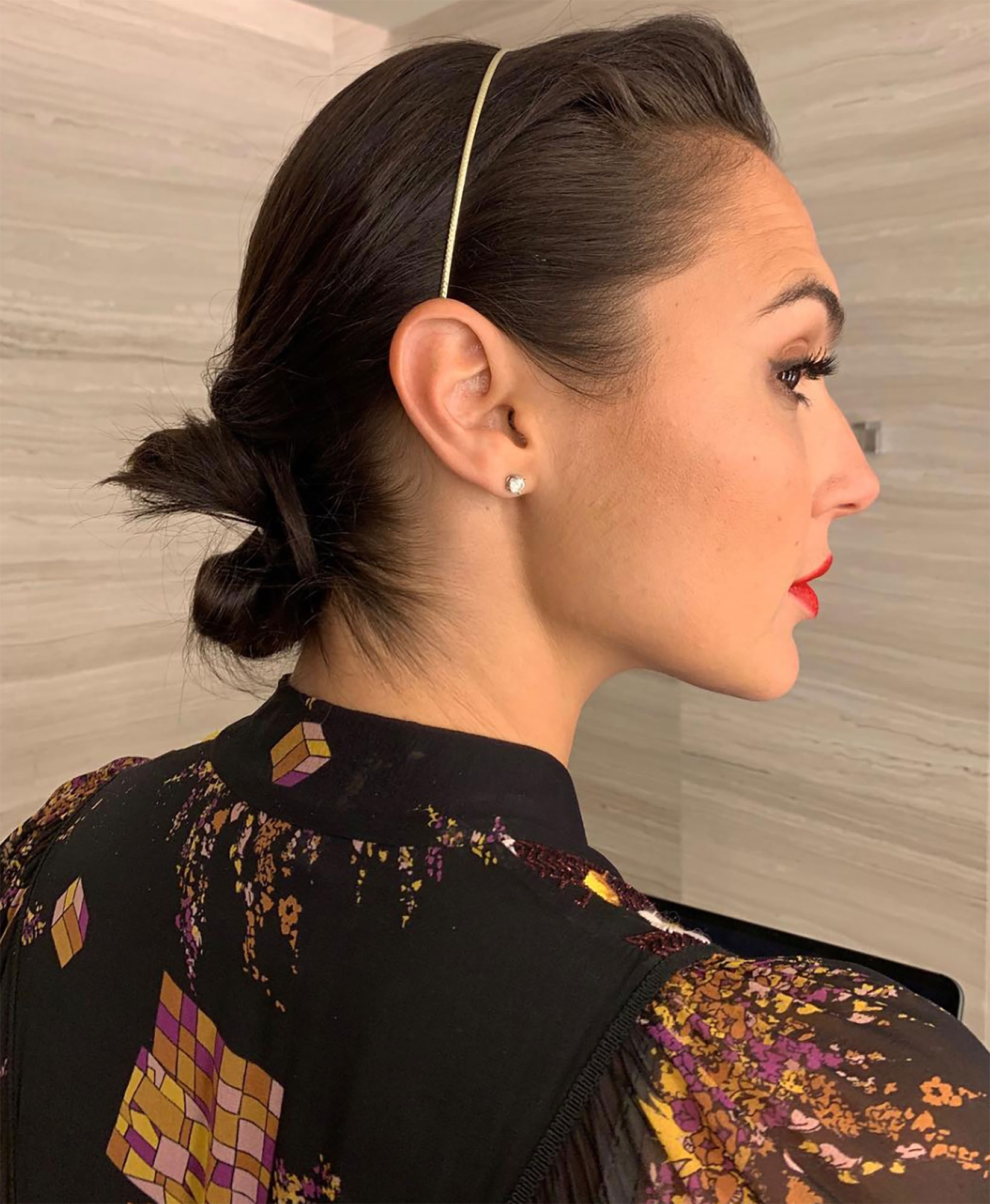 """Gal Gadot's Headband makeup red lips - Avoid sweaty strands in peak desert heat by securing them off your face with a headband. Celeb hairstylist Renato Campora added a skinny gold accessory to the cute """"#lowknot"""" look her created for the Wonder Woman star on Tuesday, April 9."""