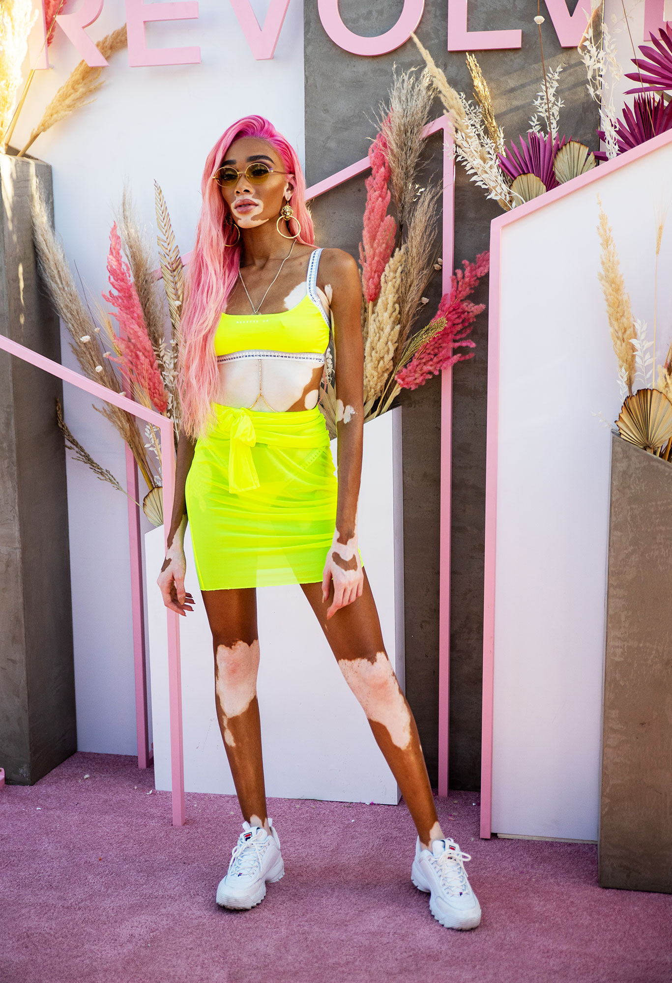 Winnie Harlow coachella fashion - The only thing cooler than the model's new pink hair? Her neon yellow skirt and bra-top combo at the Revolve Festival Saturday, April 13.
