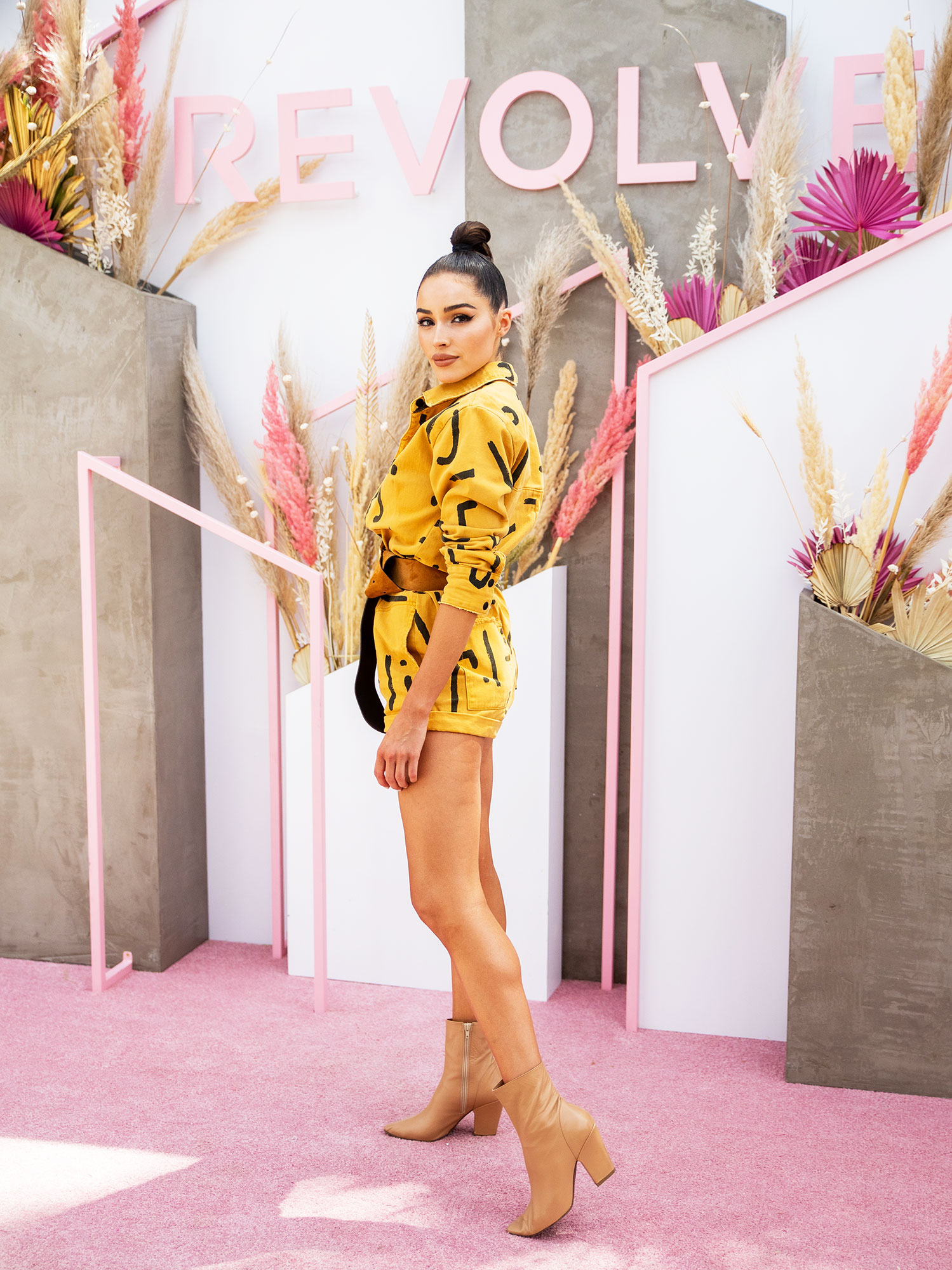 Olivia Culpo coachella fashion - Nude booties made the perfect complement to the model's yellow romper at the Revolve Festival on Sunday, April 14.