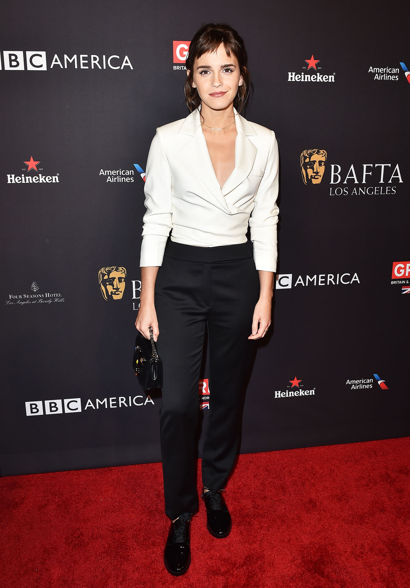 Emma Watson birthday red carpet outfits - Showing Us all how to rock chic separates on the red carpet, Watson wore a white Osman crop top with black trousers by the brand with her Susi Studio loafers and Ronald Van Der Kemp top-handle bag at the BAFTA Los Angeles Tea Party.