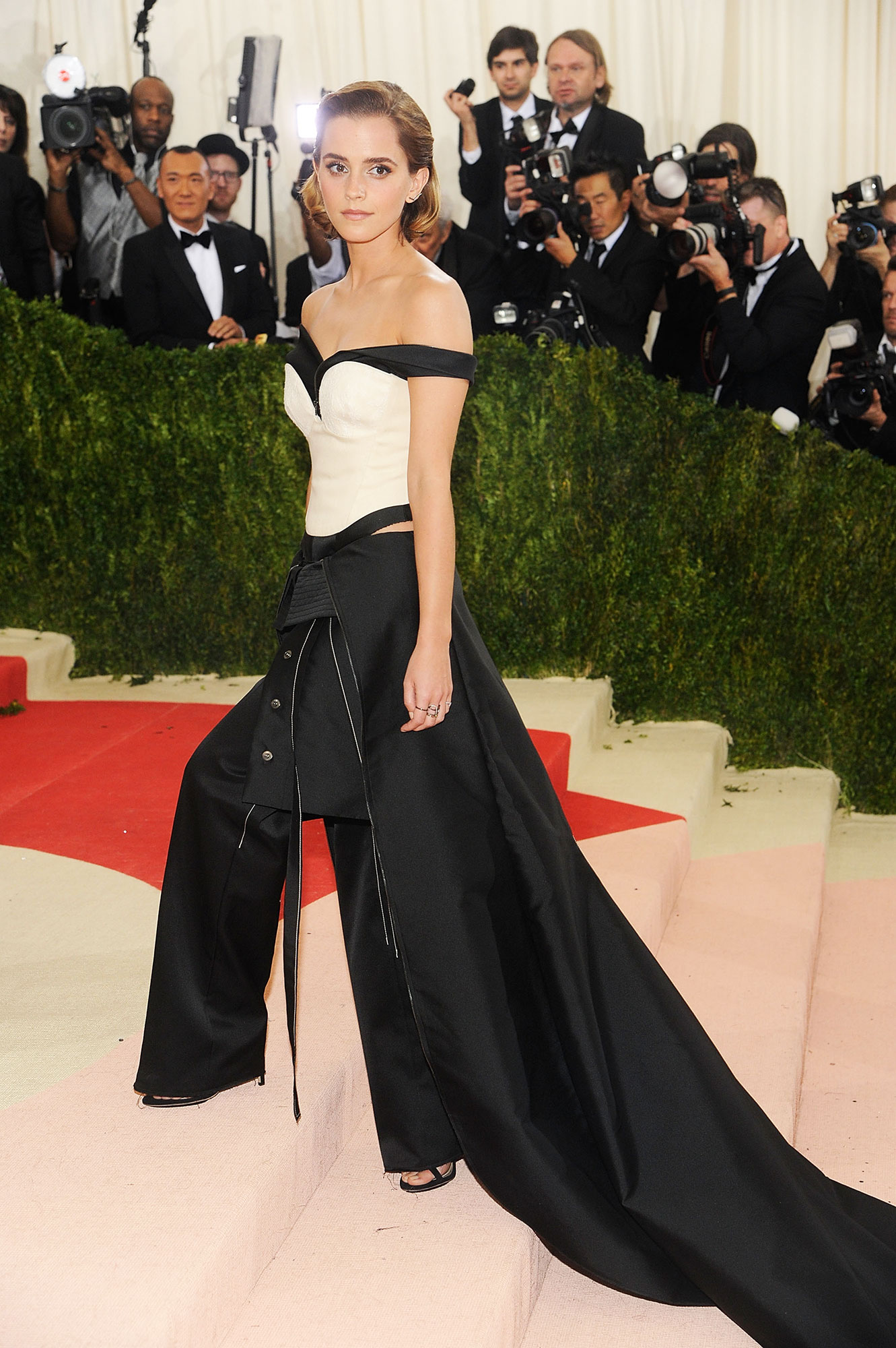 "Emma Watson birthday red carpet outfits - She chose an expertly constructed off-the-shoulder Calvin Klein pantsuit with a dramatic train for the ""Manus x Machina: Fashion In An Age Of Technology""-themed Met Gala."