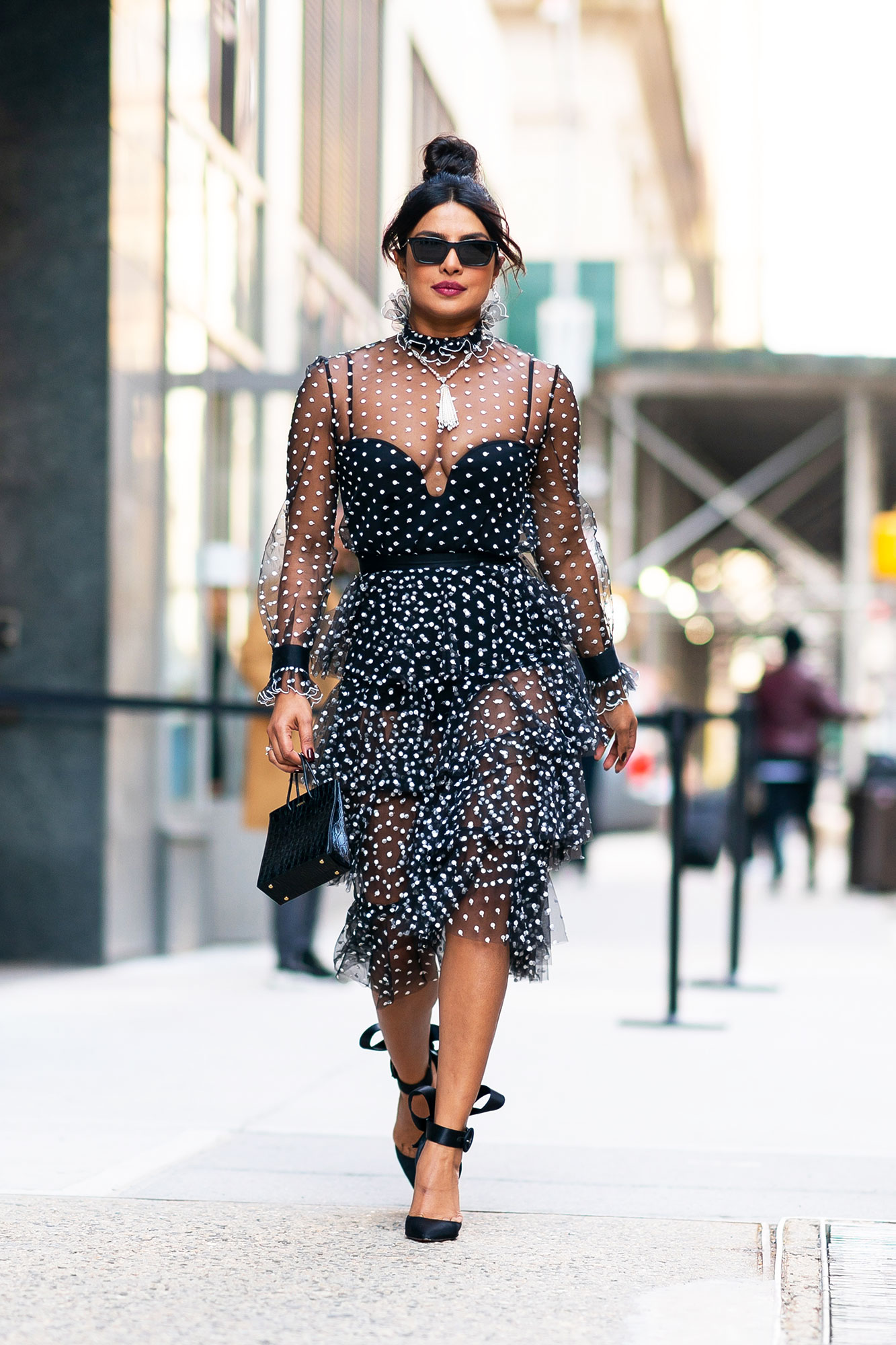 Priyanka Chopra polka dotted dress ruffles new york city - The brunette beauty stunned in a frilly Philosophy di Lorenzo Serafini sheer frock and a La Perla bodysuit in NYC. Proving more is more, she accessorized with a black Medea top-handle bag, bow-adorned Christian Louboutin heels and Chopard jewels, but we're particularly obsessed with her center-parted topknot.